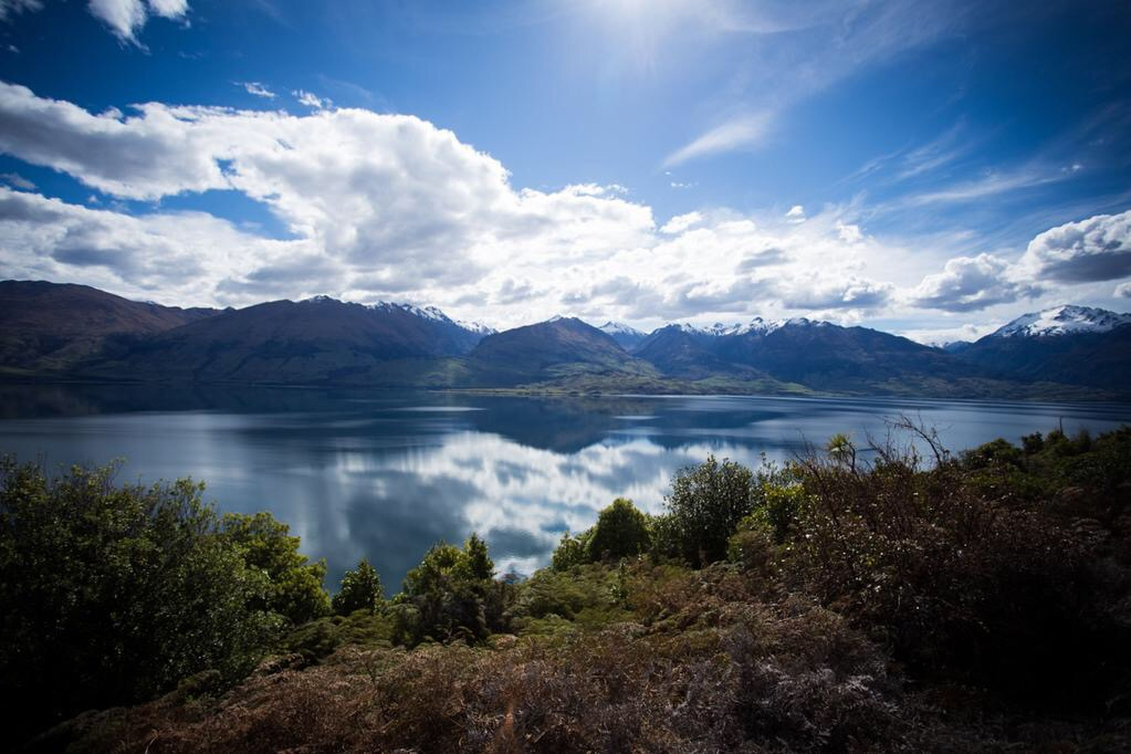 mountain, mountain range, tranquil scene, lake, tranquility, scenics, water, sky, beauty in nature, reflection, cloud - sky, nature, cloud, idyllic, landscape, non-urban scene, calm, outdoors, majestic, lakeshore