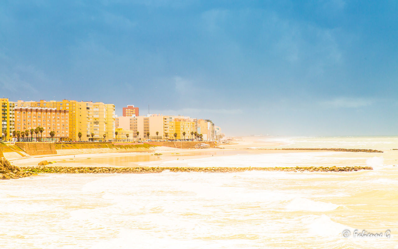 sea, beach, sky, water, architecture, sand, shore, building exterior, built structure, nature, wave, beauty in nature, cloud - sky, outdoors, no people, scenics, motion, horizon over water, day, city