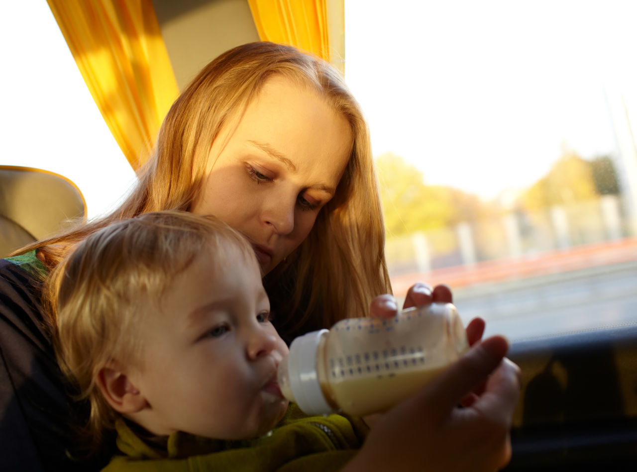 Mother Feeding Milk To Son By Window While Traveling In Bus