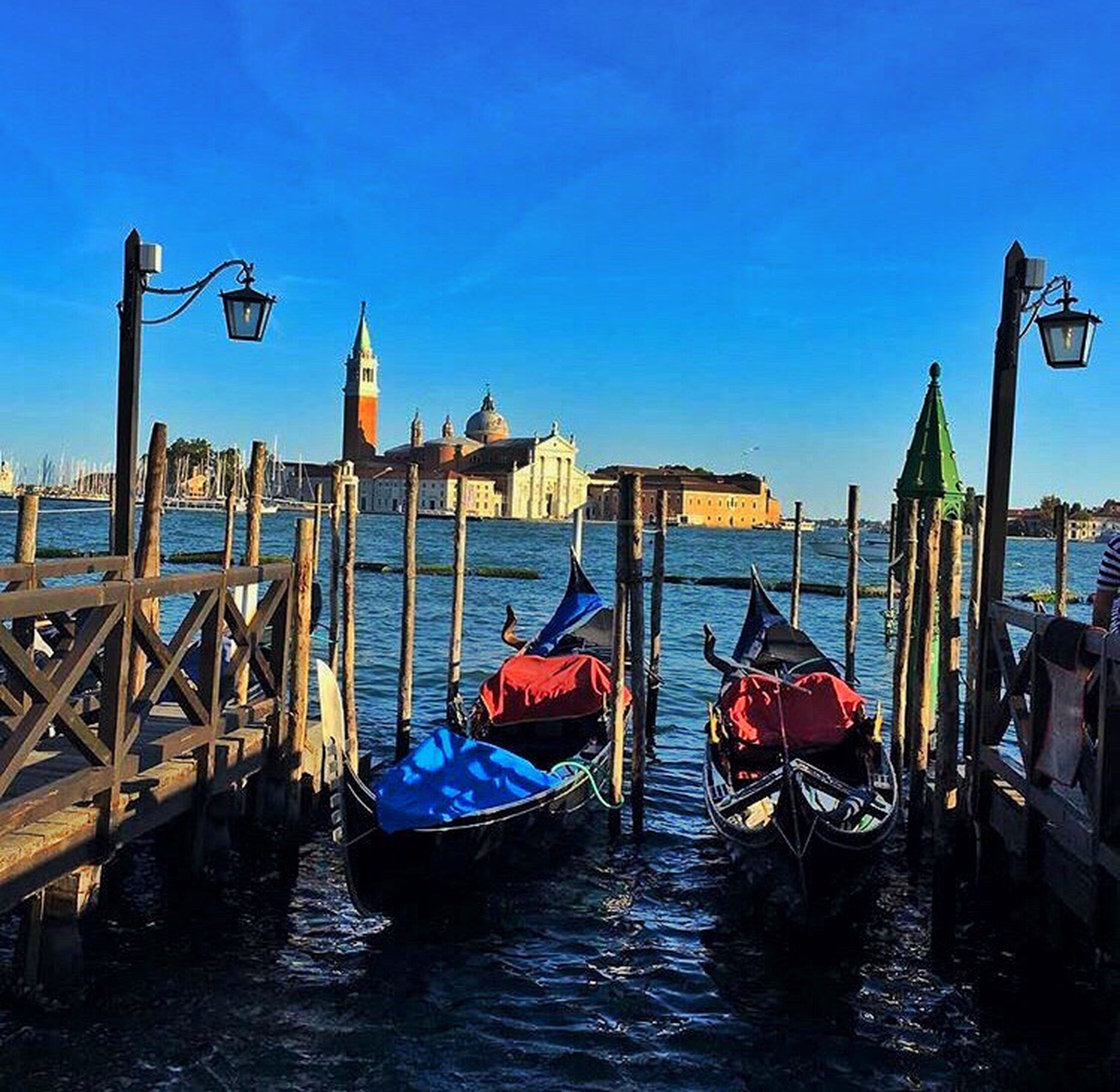 nautical vessel, boat, transportation, water, mode of transport, blue, waterfront, wooden post, culture, rippled, gondola - traditional boat, clear sky, river, multi colored, canal, in a row, sea, international landmark, tourism, tranquility, sky, famous place, day, scenics, nature, outdoors, tranquil scene