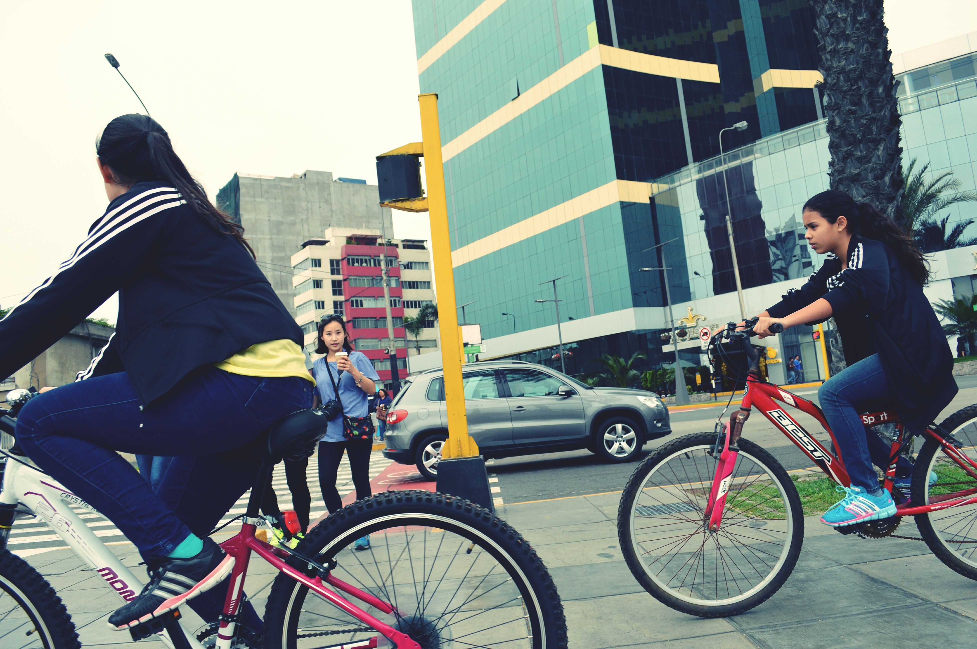 bicycle, lifestyles, transportation, land vehicle, mode of transport, architecture, building exterior, leisure activity, built structure, casual clothing, men, city, riding, street, city life, standing, full length, day