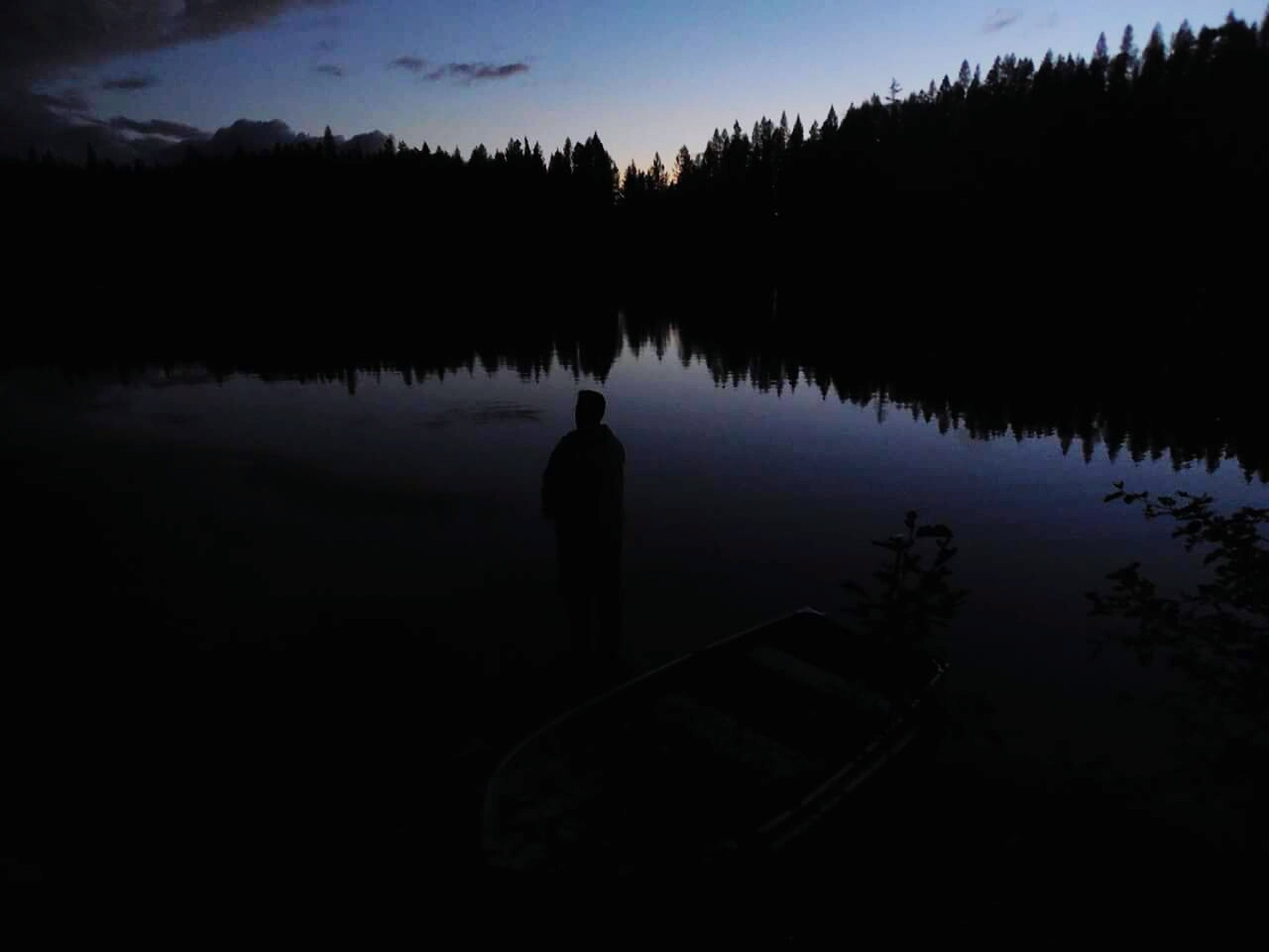 silhouette, water, lake, tranquility, reflection, sky, tranquil scene, scenics, sunset, beauty in nature, dusk, nature, tree, calm, blue, outdoors, idyllic, standing water, lakeshore, one person