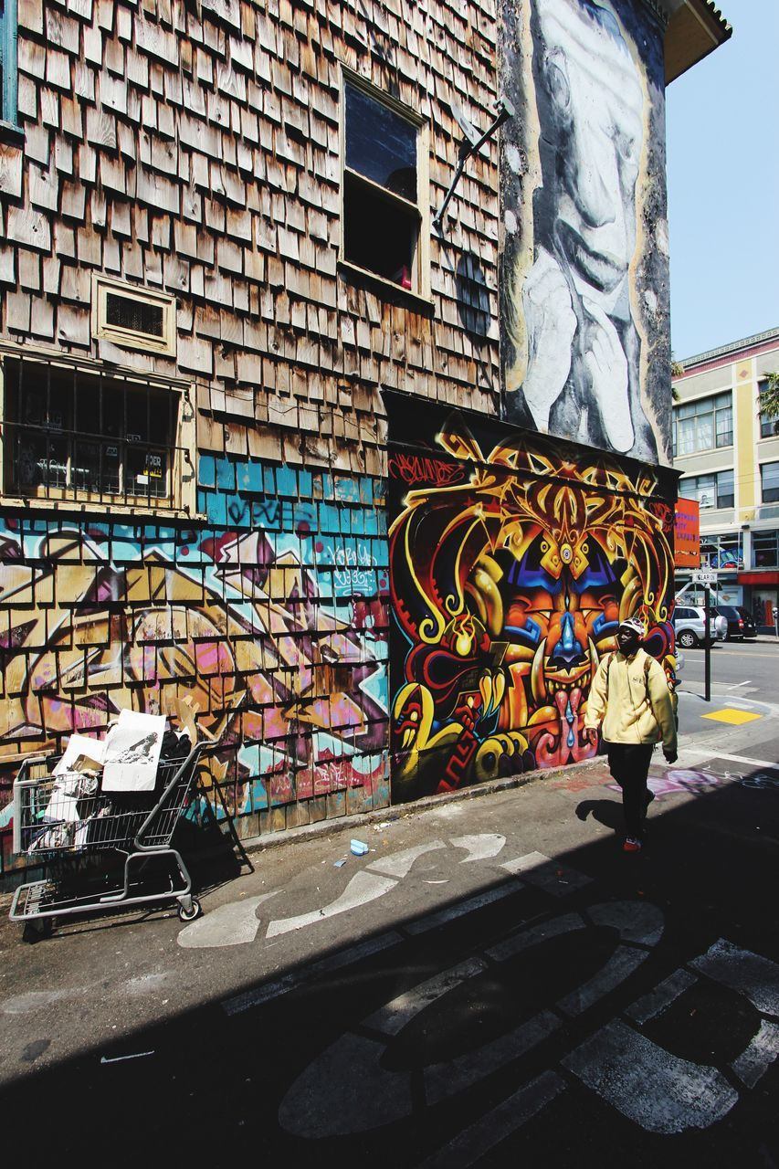 building exterior, architecture, built structure, graffiti, art and craft, creativity, multi colored, real people, street art, outdoors, day, men, standing, city, one person, people