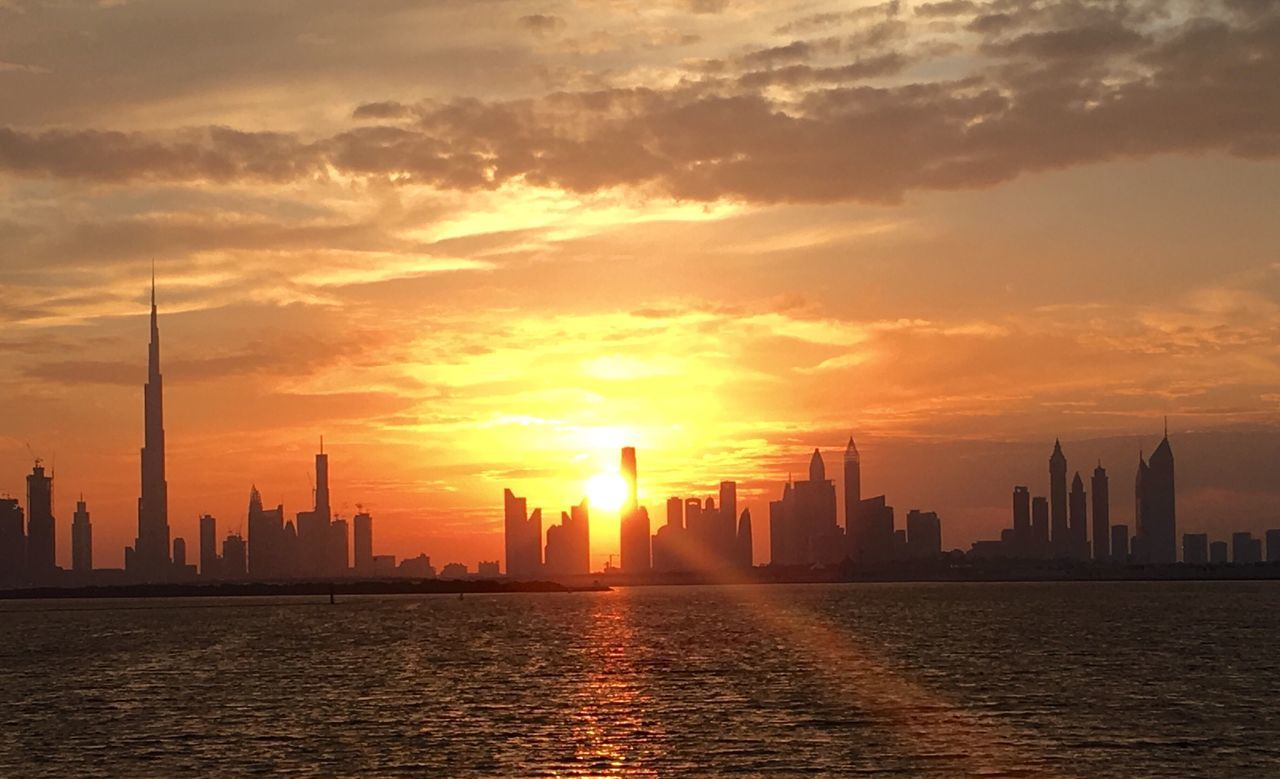 Burj Khalifa By River Against Sky During Sunset In City