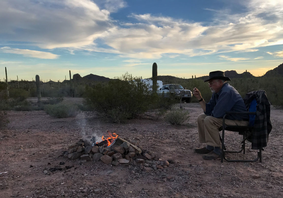 Man Sitting by Campfire at Sunset Campfire Camping Rving Casual Clothing Cloud - Sky Leisure Activity Lifestyles Nature One Person Outdoors Relaxation Sitting Sky Sunset