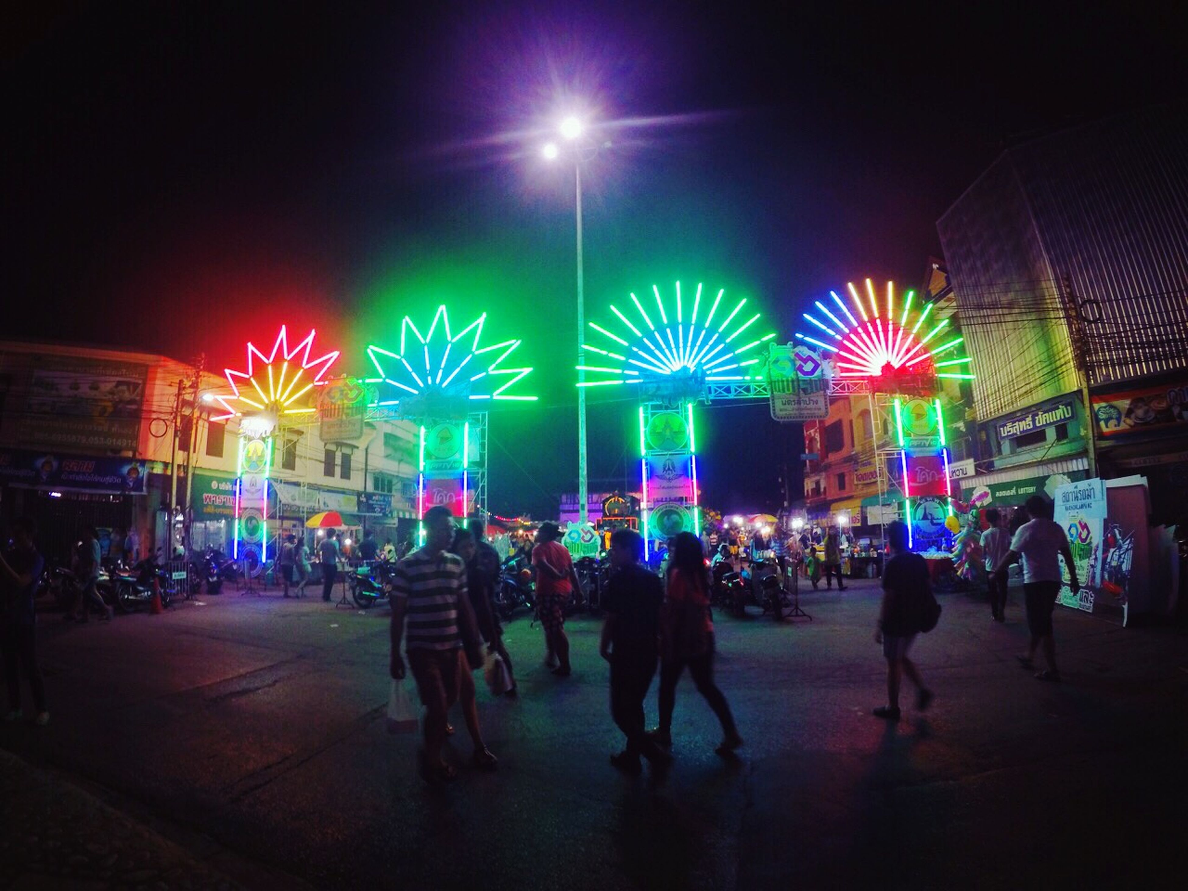 illuminated, night, large group of people, lighting equipment, lifestyles, men, leisure activity, built structure, arts culture and entertainment, architecture, building exterior, person, celebration, city, city life, crowd, mixed age range, light - natural phenomenon, group of people