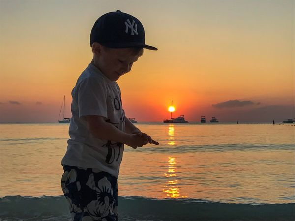 Sunset Sea Beach Water Orange Color Beauty In Nature Sun Real People Sky Scenics Nature Standing Outdoors Reflection Vacations Lifestyles Horizon Over Water One Person Leisure Activity Side View Gerrits An Eye For Travel