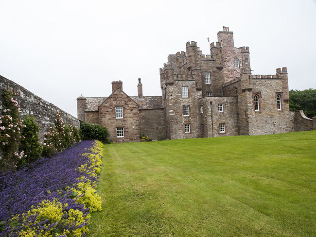 The Queen Mothers Castle of Mey Scotland.The castle was in a semi-derelict state when, in 1952, it and its policies (attached lands) were purchased by Queen Elizabeth The Queen Mother, the widow of King George VI who had died earlier in the year. The Queen Mother set about restoring the castle for use as a holiday home, removing some of the 19th-century additions, and reinstating the Castle's original name. She regularly visited it in August and October from 1955 until her death in March 2002, the last visit being in October 2001. Ancient Architecture Building Exterior Built Structure Castle Castle Castle Of Mey Damaged Day History Medieval Old Old Ruin Outdoors Ruin Ruined Scotland. Sky Surface Level The Past The Queen Mother Tourism Travel Destinations Vivid International Weathered