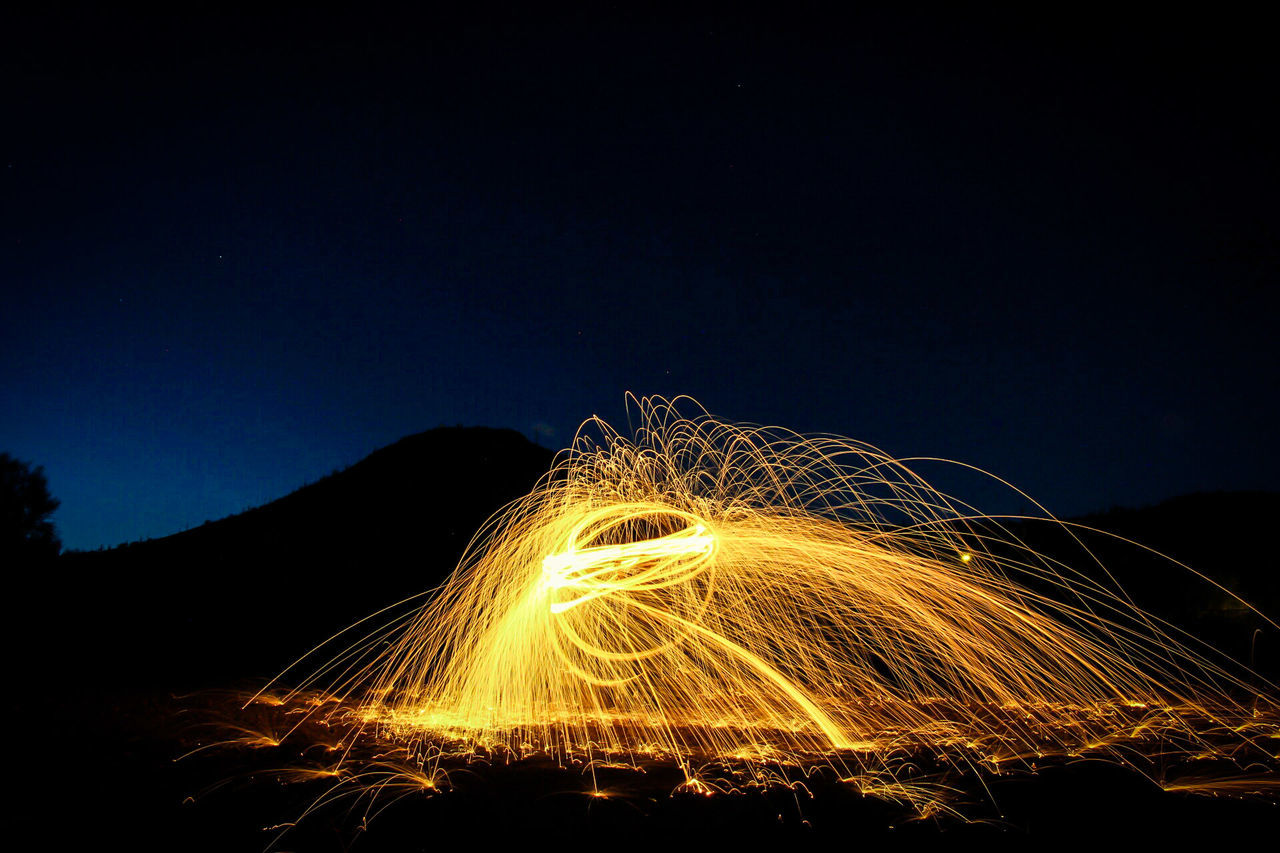 night, long exposure, motion, illuminated, wire wool, light painting, speed, formation, light trail, outdoors, sky, clear sky, no people, arts culture and entertainment, nature