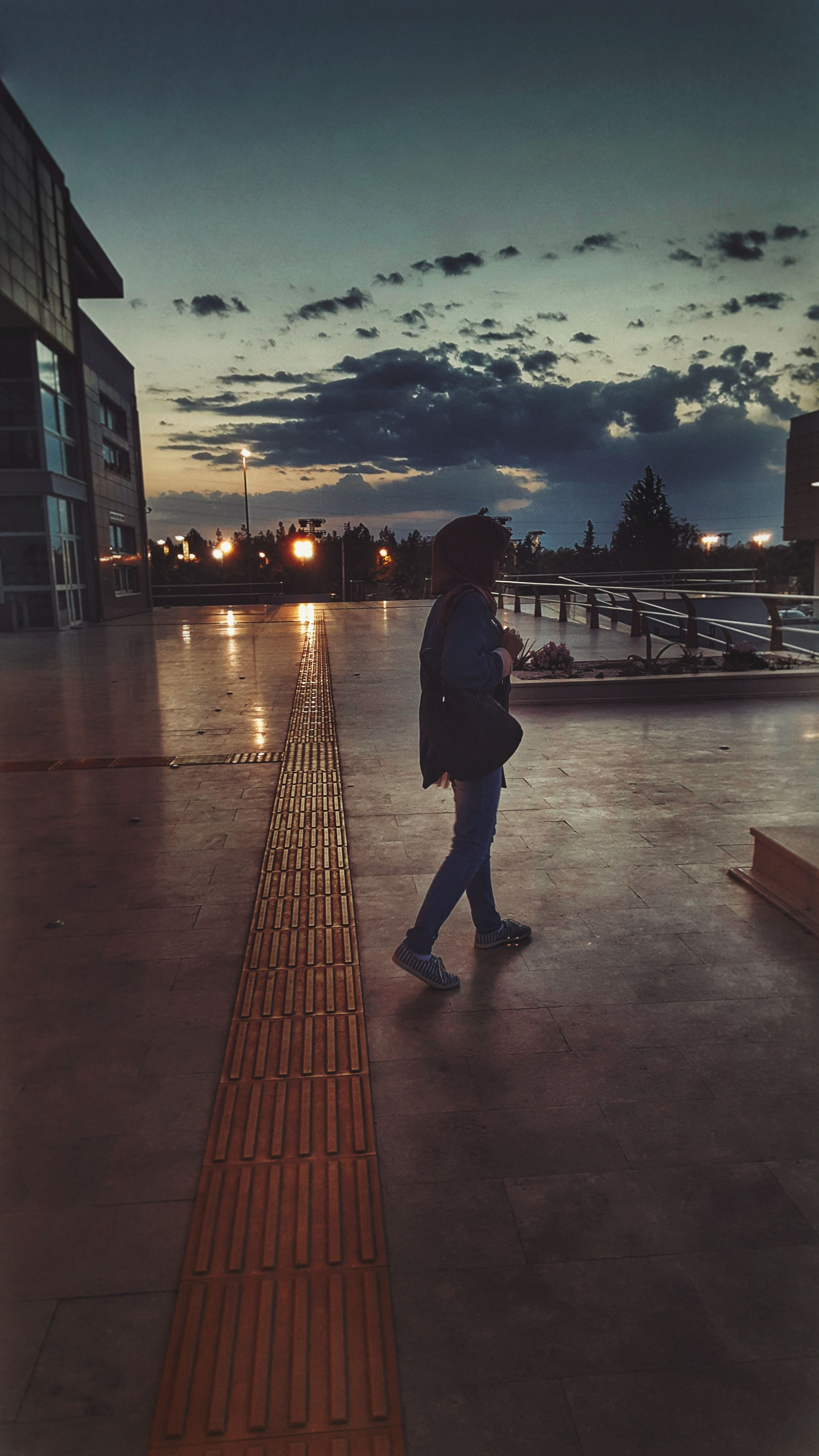 real people, lifestyles, leisure activity, water, building exterior, full length, sky, men, built structure, architecture, outdoors, one person, sunset, illuminated, women, city, people, nature, adults only, adult, cityscape, night