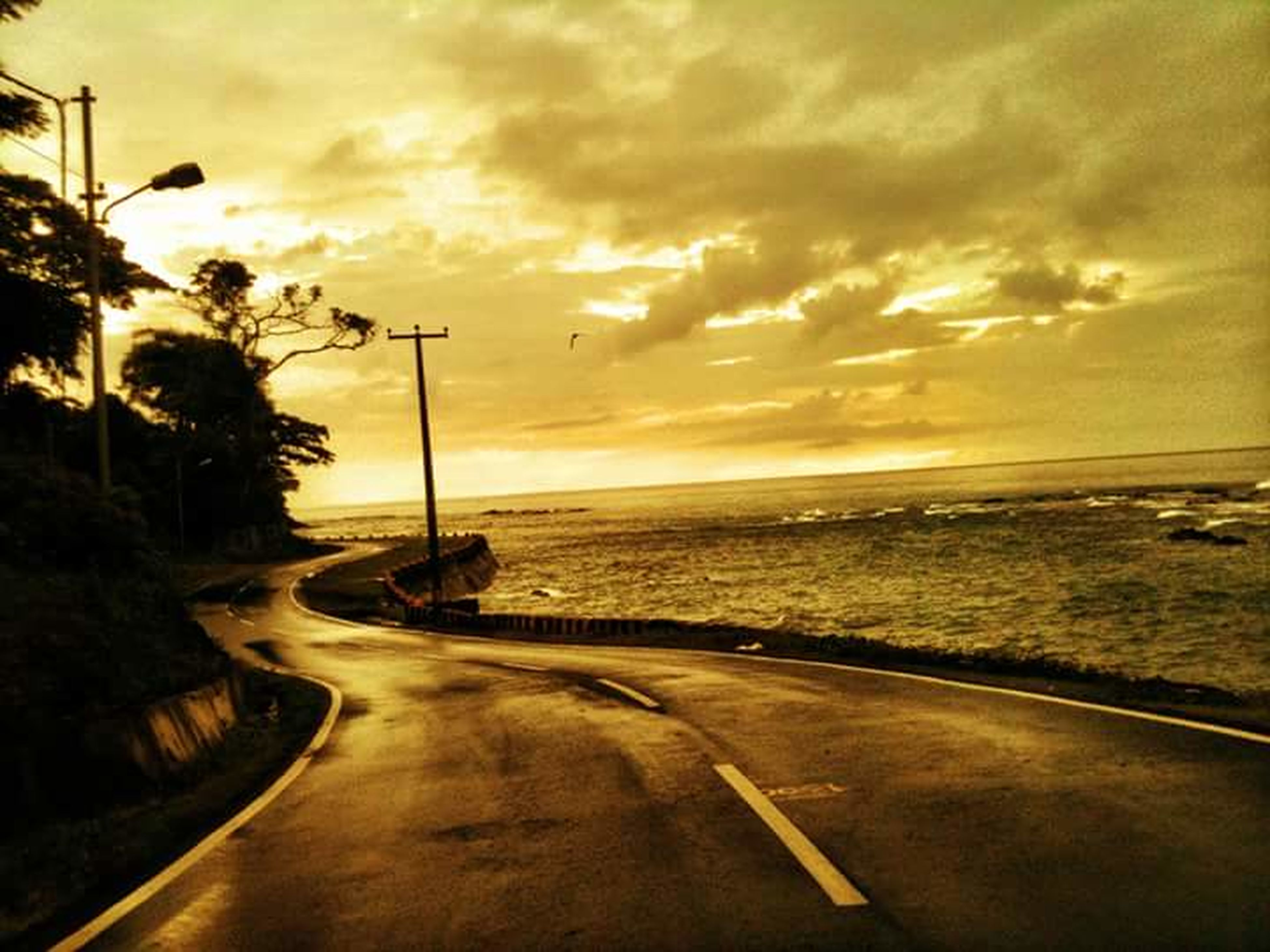 sunset, sky, sea, road, water, cloud - sky, the way forward, horizon over water, scenics, tranquil scene, tranquility, beauty in nature, beach, transportation, cloudy, cloud, nature, dramatic sky, diminishing perspective, street