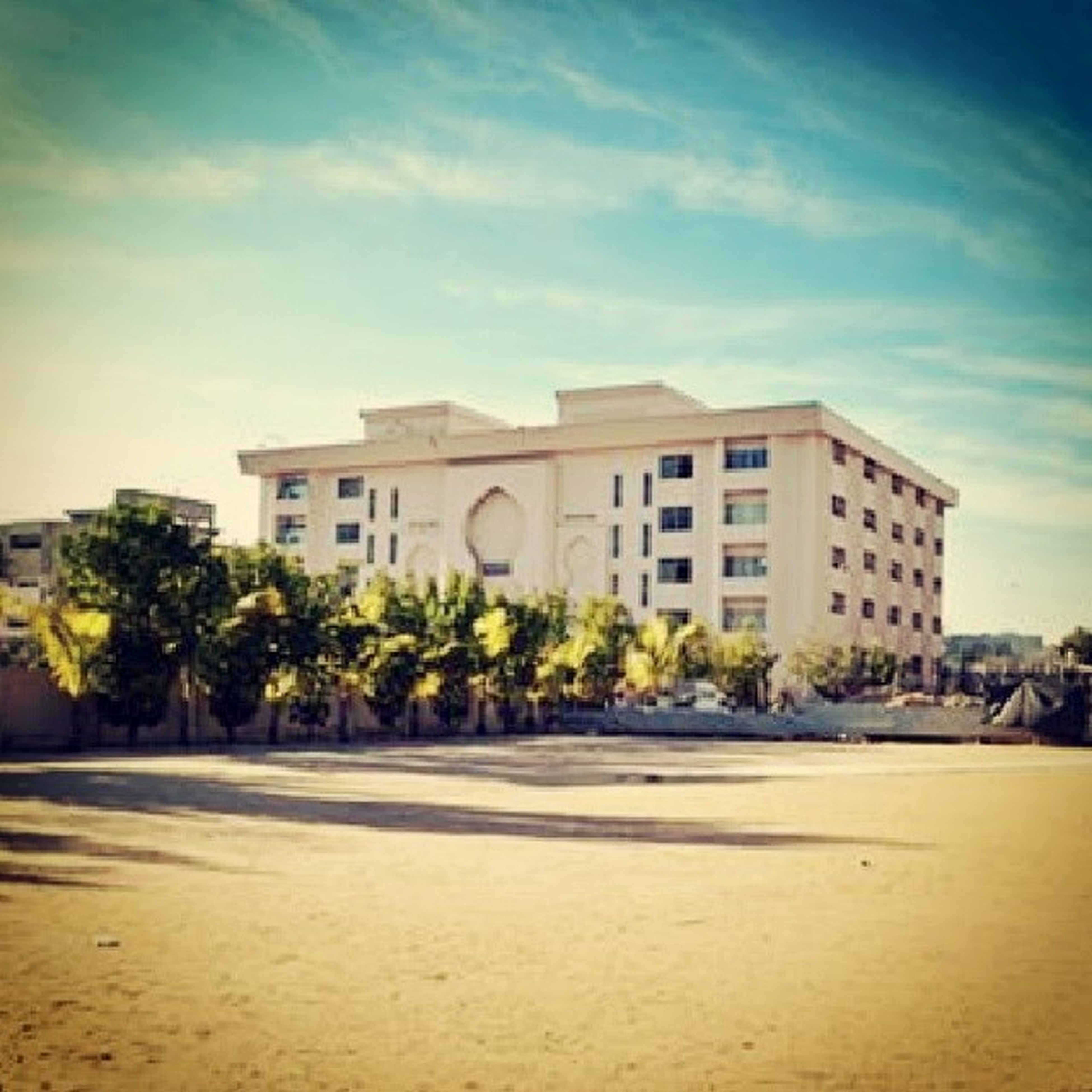 architecture, building exterior, built structure, sky, tree, palm tree, cloud - sky, cloud, house, sand, beach, sunlight, residential structure, day, outdoors, residential building, building, facade, incidental people, travel destinations