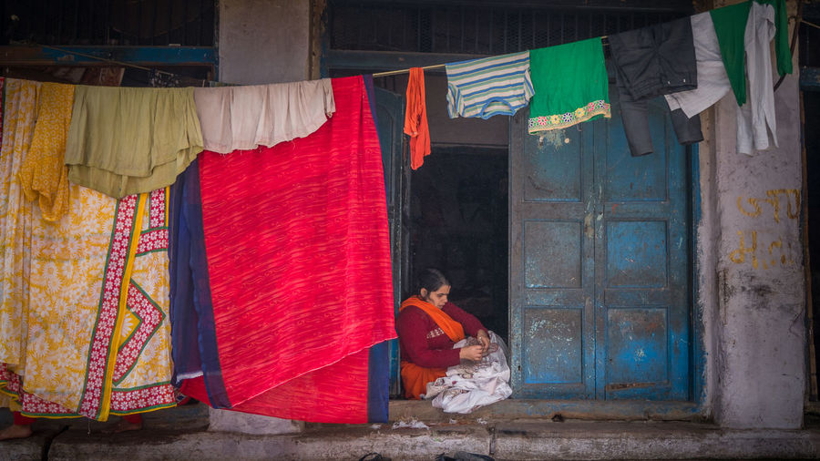 Asian  India Indian Lifestyle Sitting Sitting Outside Cloth Drying Hanging Indian Womn Lifestyle Photography Lifestyles One Person Outdoors People Real People Sari Textile Traditional Clothing Women