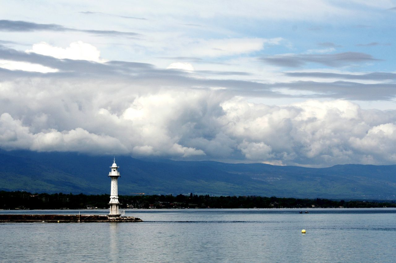 lighthouse, guidance, cloud - sky, direction, sky, architecture, safety, day, built structure, protection, building exterior, scenics, water, nature, outdoors, sea, tranquility, no people, waterfront, tranquil scene, beauty in nature, mountain