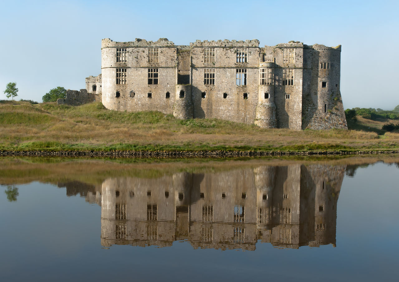 Carew Castle overlooks the tidal mill pond on the Carew River. The north face of the Norman castle was later transformed into an Elizabethan mansion. Carew Castle Elizabethan History No People Norman Old Ruin Outdoors Pembrokeshire Reflection Tree Wales Water Waterfront EyeEmNewHere