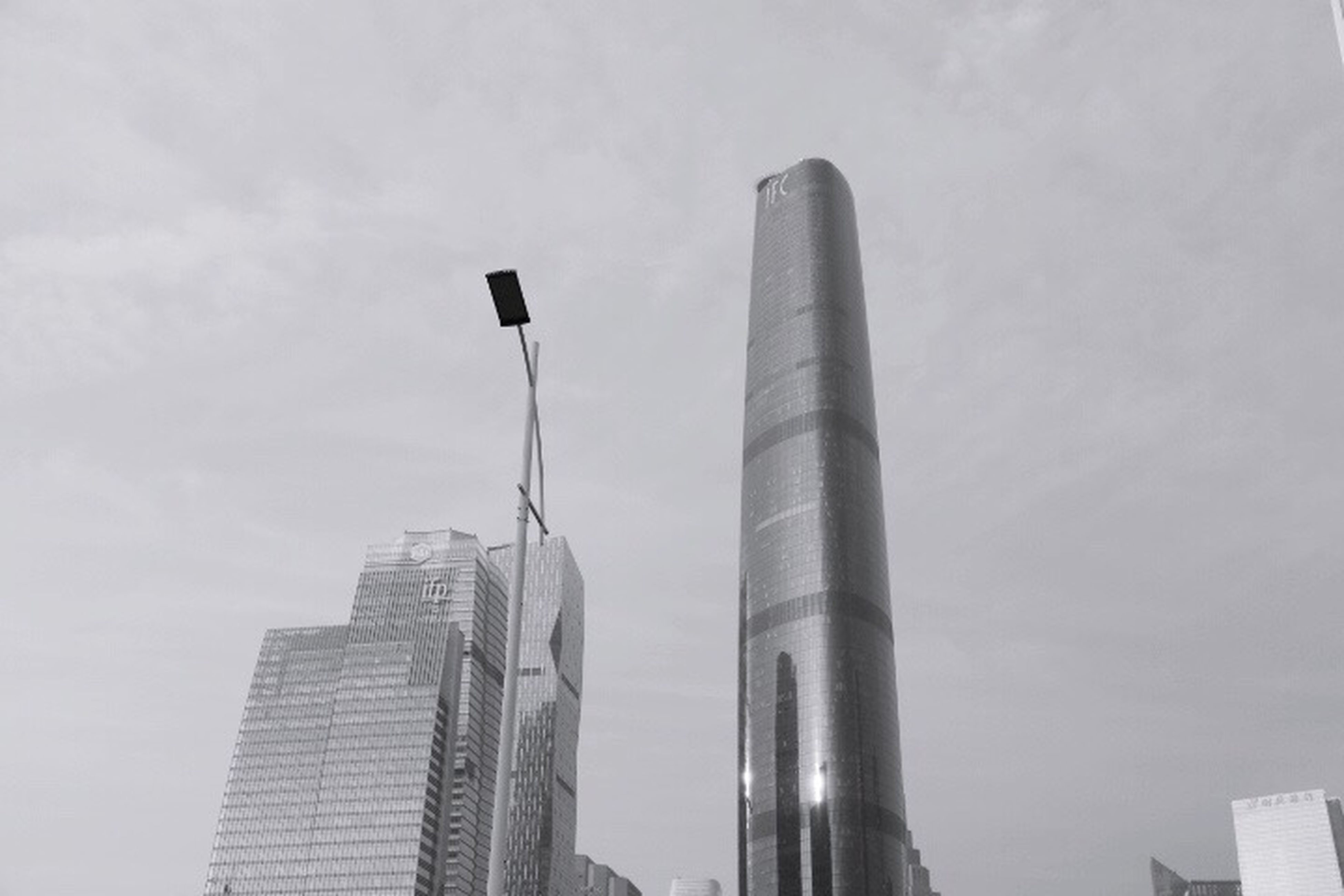 low angle view, building exterior, architecture, built structure, tall - high, sky, skyscraper, city, tower, office building, modern, street light, building, tall, day, cloud - sky, outdoors, no people, cloud, cloudy