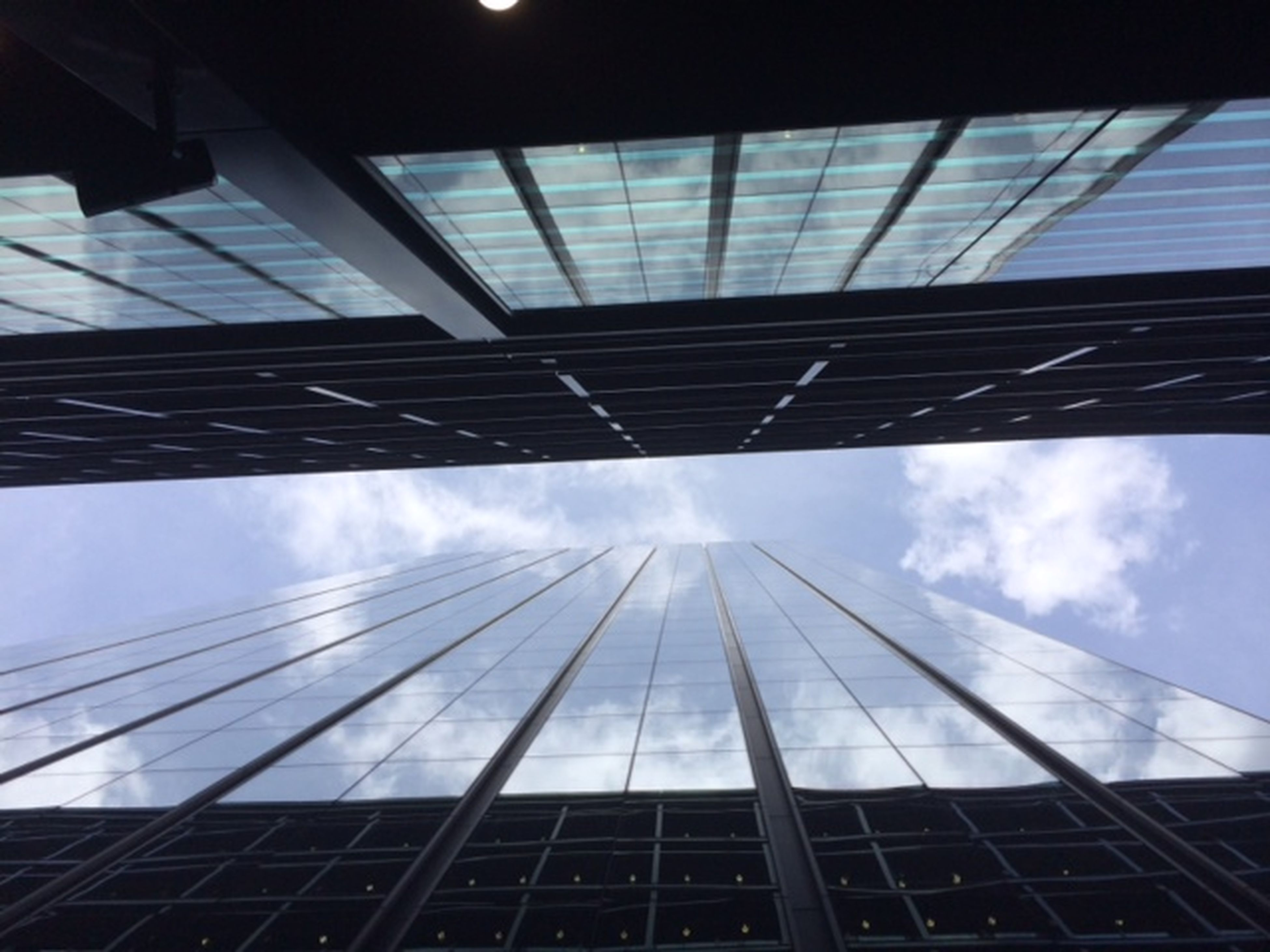architecture, built structure, low angle view, modern, building exterior, office building, glass - material, skyscraper, city, sky, tall - high, reflection, tower, directly below, building, cloud - sky, day, glass, architectural feature, no people