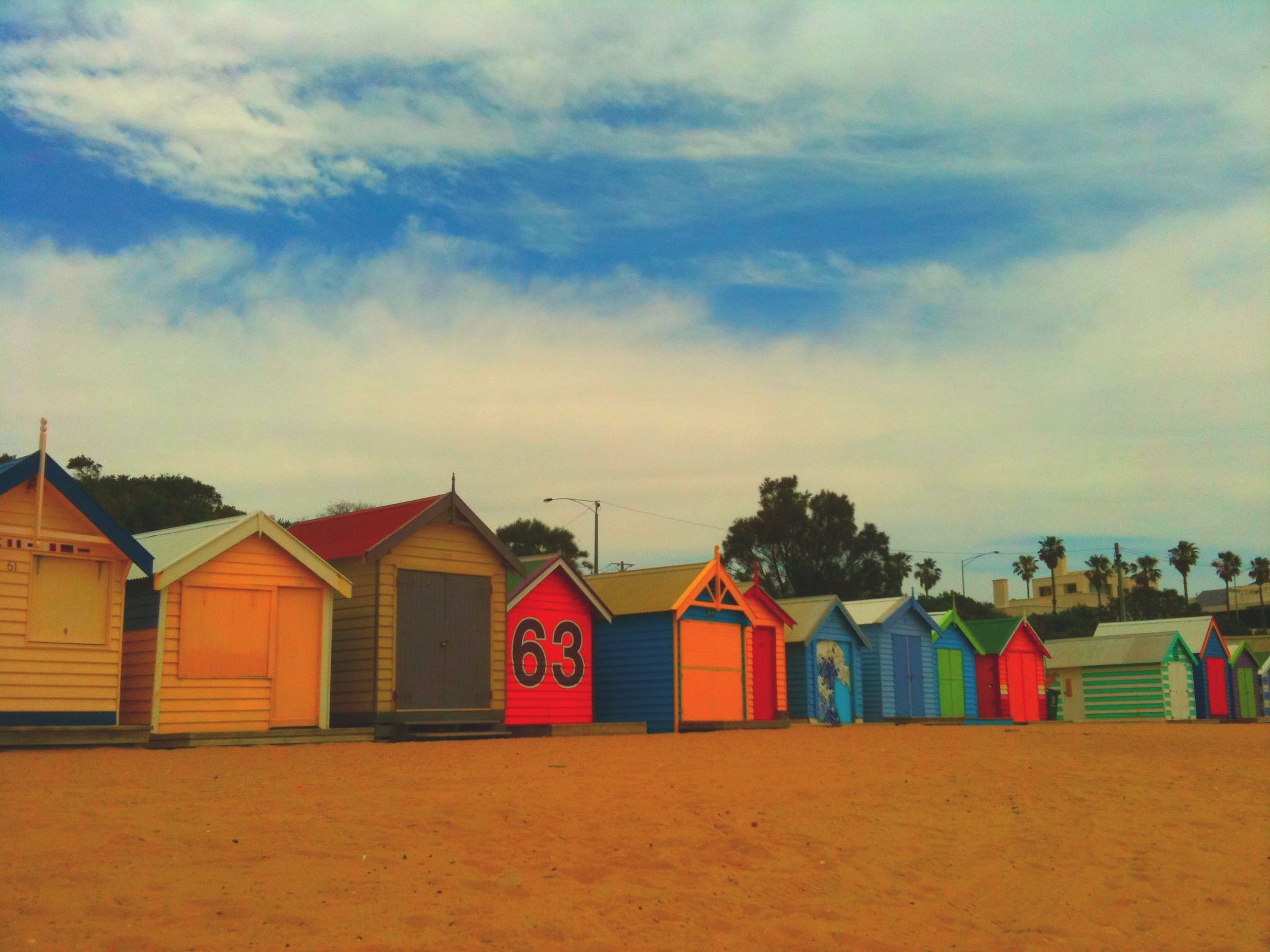 sky, built structure, architecture, building exterior, multi colored, cloud - sky, house, cloud, in a row, sand, colorful, cloudy, outdoors, beach, day, roof, nature, beach hut, no people, tranquility