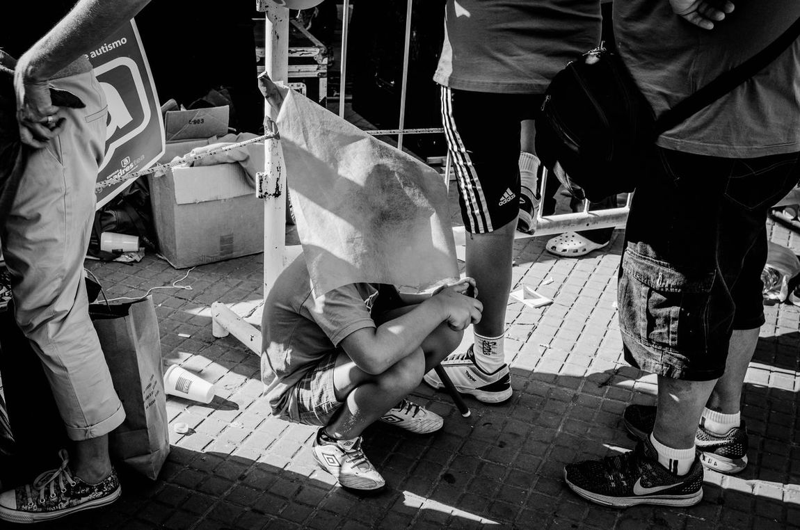 A boy with autism spectrum hides in the middle of the mobilization for International Autism Day. In Plaza de Mayo, City of Buenos AiresThe Photojournalist - 2017 EyeEm Awards Childrenportraits Children ChildhoodLow Section Autism Autism Awareness Autistic Child WorldAutismAwarenessDay TGD Real People Human Leg Men Adults Only Outdoors People Adult Women Day Only Men Human Body Part One Person Close-up Young Adult First Eyeem Photo
