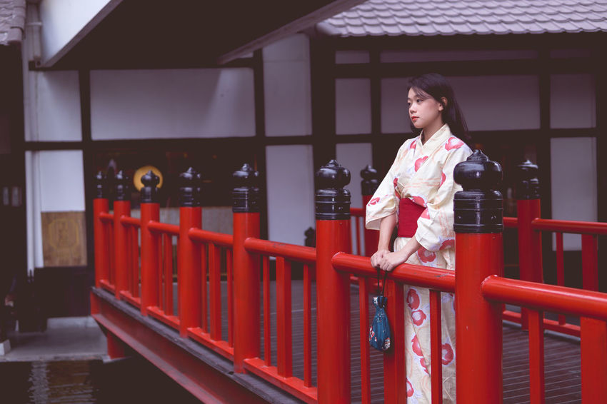 Architecture Beautiful Woman Built Structure Casual Clothing Day Front View Full Length Kimono Leisure Activity Lifestyles One Person Outdoors Railing Real People Red Standing Walking Young Adult Young Women