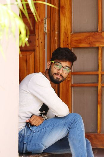 Only Men One Man Only Adults Only One Person Sitting Adult People Casual Clothing Men Eyeglasses  Beard Portrait Armchair Indoors  Day Young Adult Brown Background Litte Greenary Stylish Man Stylish Hairstyle.  Door As Background Looking At Camera Canon Photography ©apTa!n The Portraitist - 2017 EyeEm Awards