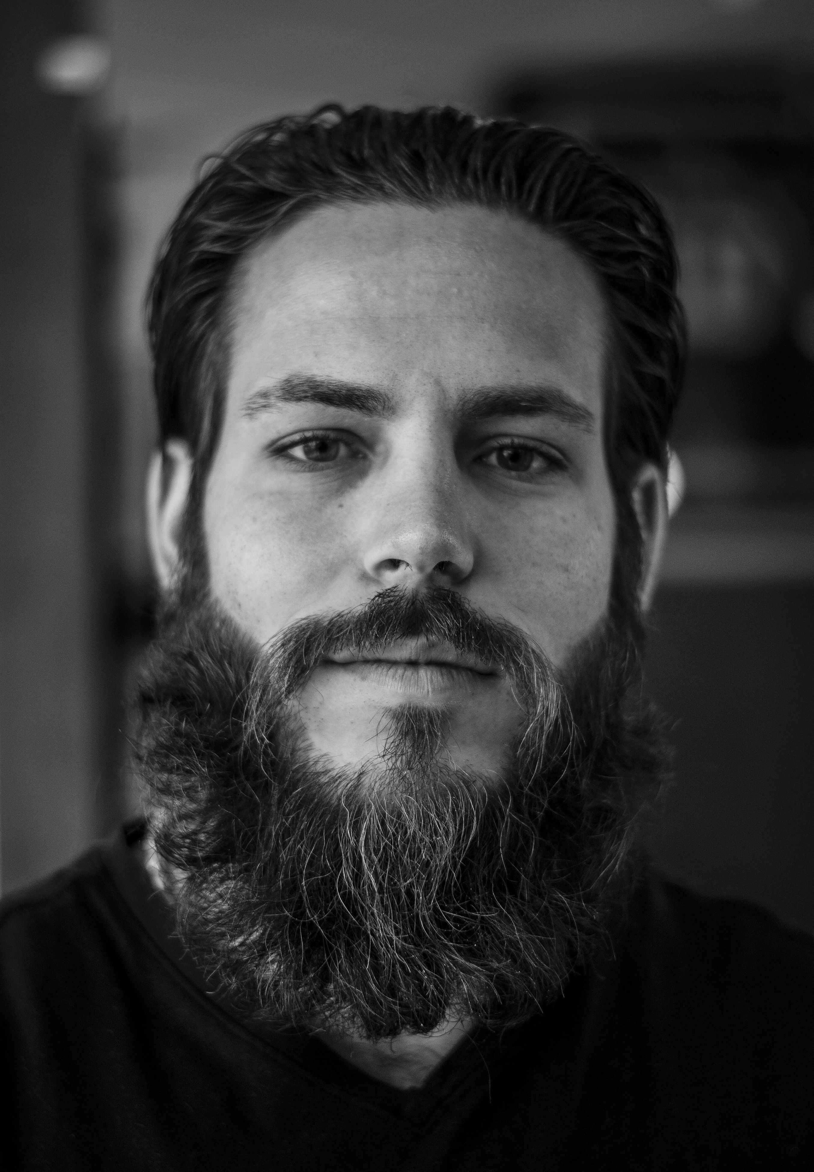 indoors, lifestyles, headshot, portrait, looking at camera, leisure activity, young adult, person, front view, young men, close-up, casual clothing, beard, home interior, focus on foreground, men, human face, mid adult