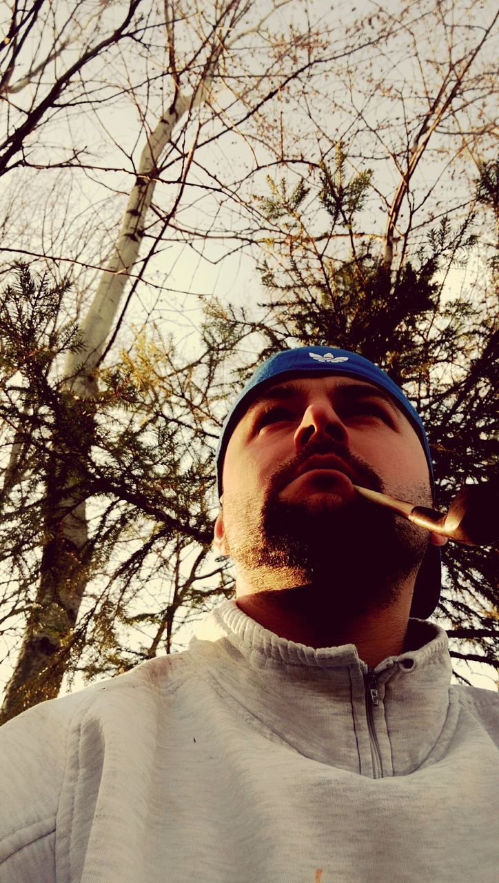 tree, one person, real people, front view, winter, cold temperature, young men, branch, young adult, day, headshot, lifestyles, bare tree, leisure activity, outdoors, beard, portrait, nature, close-up, warm clothing, sky, people
