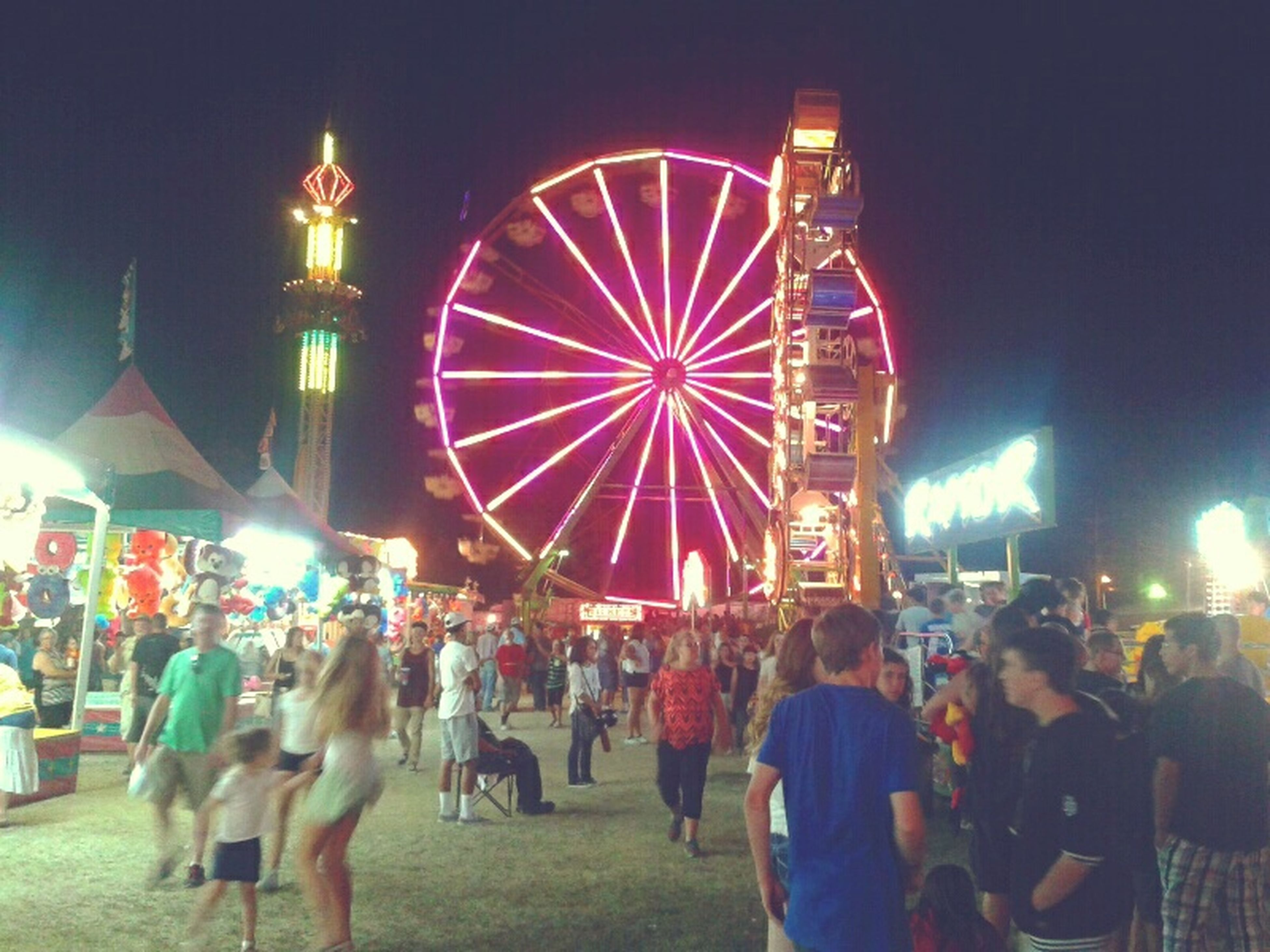 illuminated, night, arts culture and entertainment, amusement park ride, amusement park, large group of people, leisure activity, ferris wheel, architecture, building exterior, built structure, celebration, sky, person, lifestyles, men, multi colored, city, incidental people