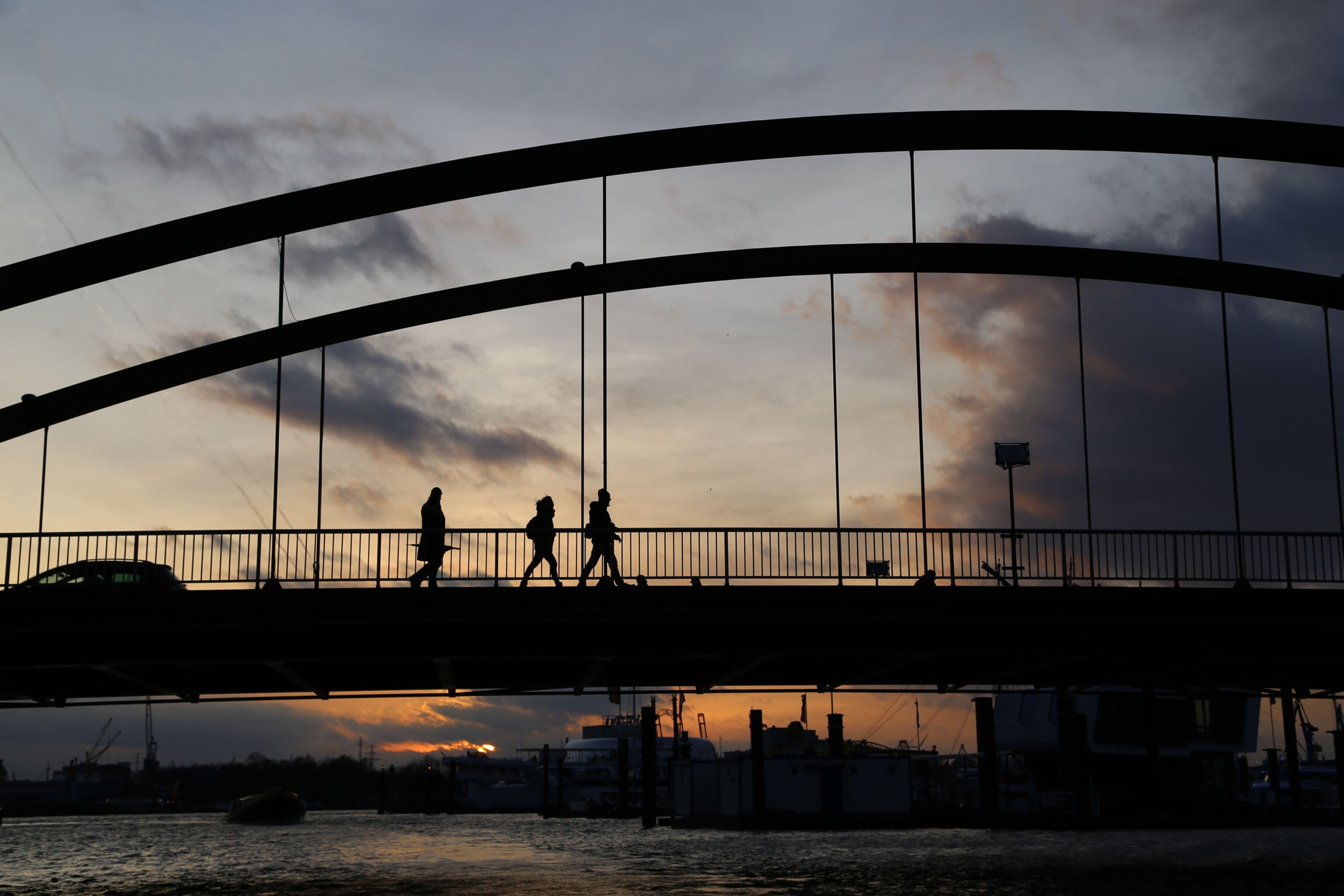 bridge - man made structure, connection, architecture, built structure, silhouette, men, sky, water, railing, lifestyles, walking, bridge, sunset, cloud - sky, transportation, engineering, leisure activity, person