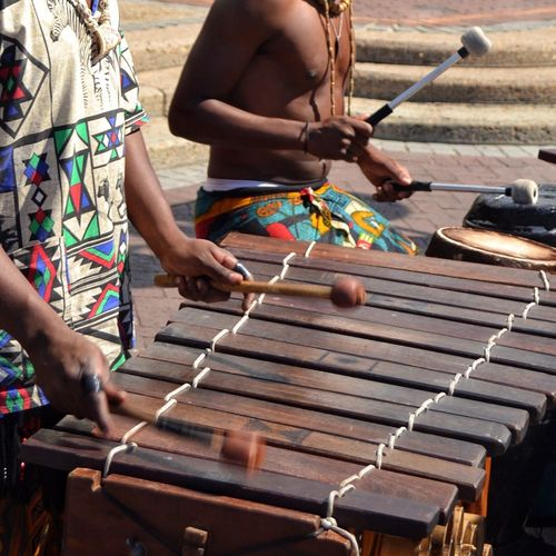 Musicians playing in a public area. TakeoverMusic Real People African Music Outdoors People Day Adult Human Hand Wood Instrument Hammer Mallets Swing In Motion South Africa Cape Town Street Musicians Street Music Buskers Bare Chest
