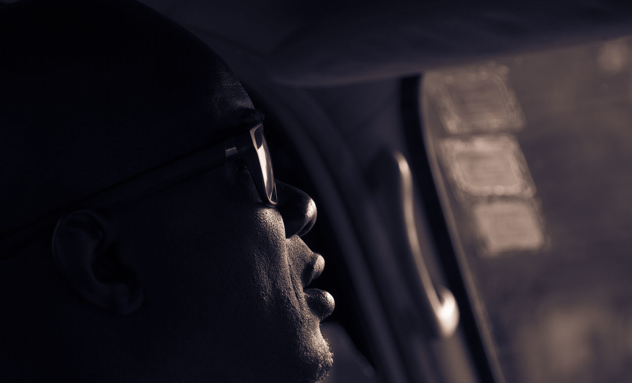 Profile of Senegalese taxi driver taken close up while driving with low sunlight. African, Behind The Wheel, Black, Car, Close-up Dark, Drive, MeinAutomoment Natural Light Portrait Journey, Man, Profile, Selective Focus Senegal, Shadow,sillouette Sunglasses, Sunlight, Shades And Shadows Fresh On Eyeem  Trip, Excursion, Journey, Tour, Tourist, Visit, Vacation, Get -away, Holiday, Interior, Mode Of Transport Taxi, Dramatic, Headshot Feel The Journey,