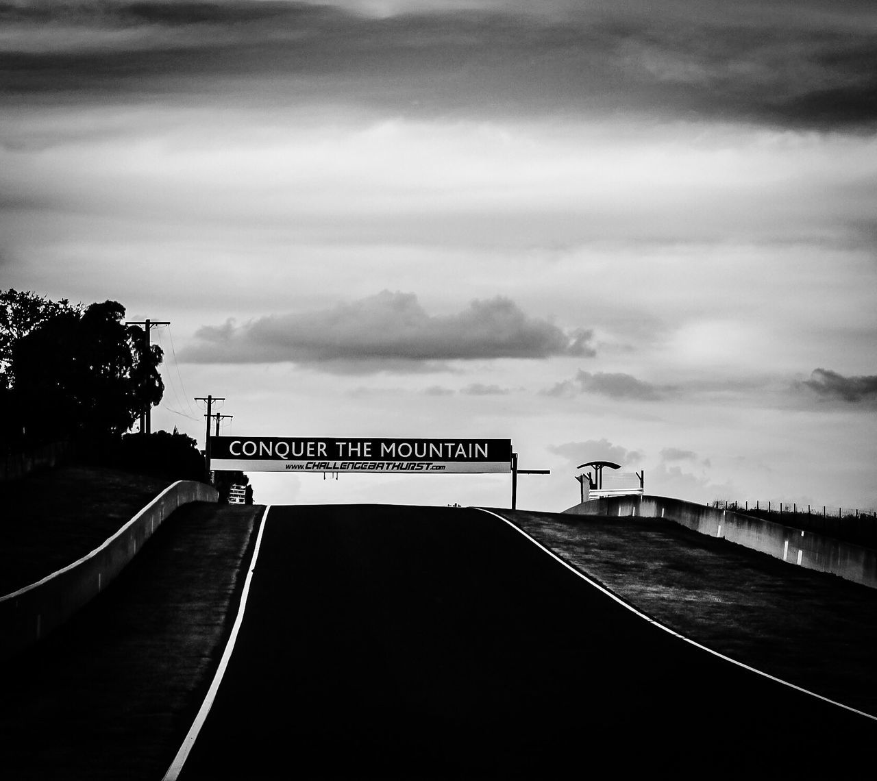 Conquer the Mountain Mount Panorama Bathurst Australia Empty Racetrack Race Track Public Road Motorsport Black And White Collection  Communication Text Cloud - Sky Transportation Sky Direction Guidance No People Road Road Sign Outdoors Day Travel Destinations