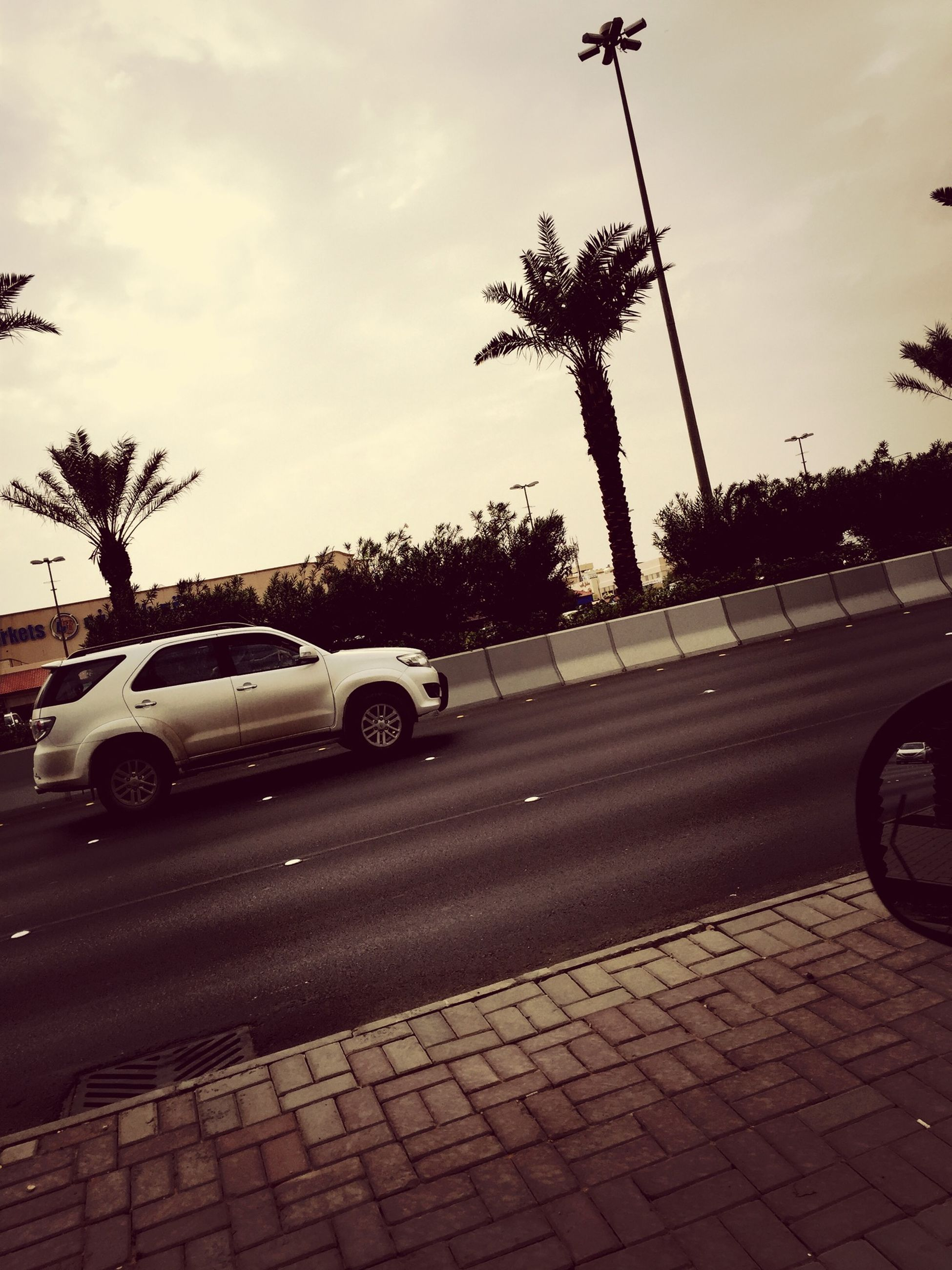 transportation, land vehicle, car, mode of transport, road, street, sky, tree, road marking, cloud - sky, palm tree, on the move, street light, traffic, cloud, travel, city street, city, outdoors, parking