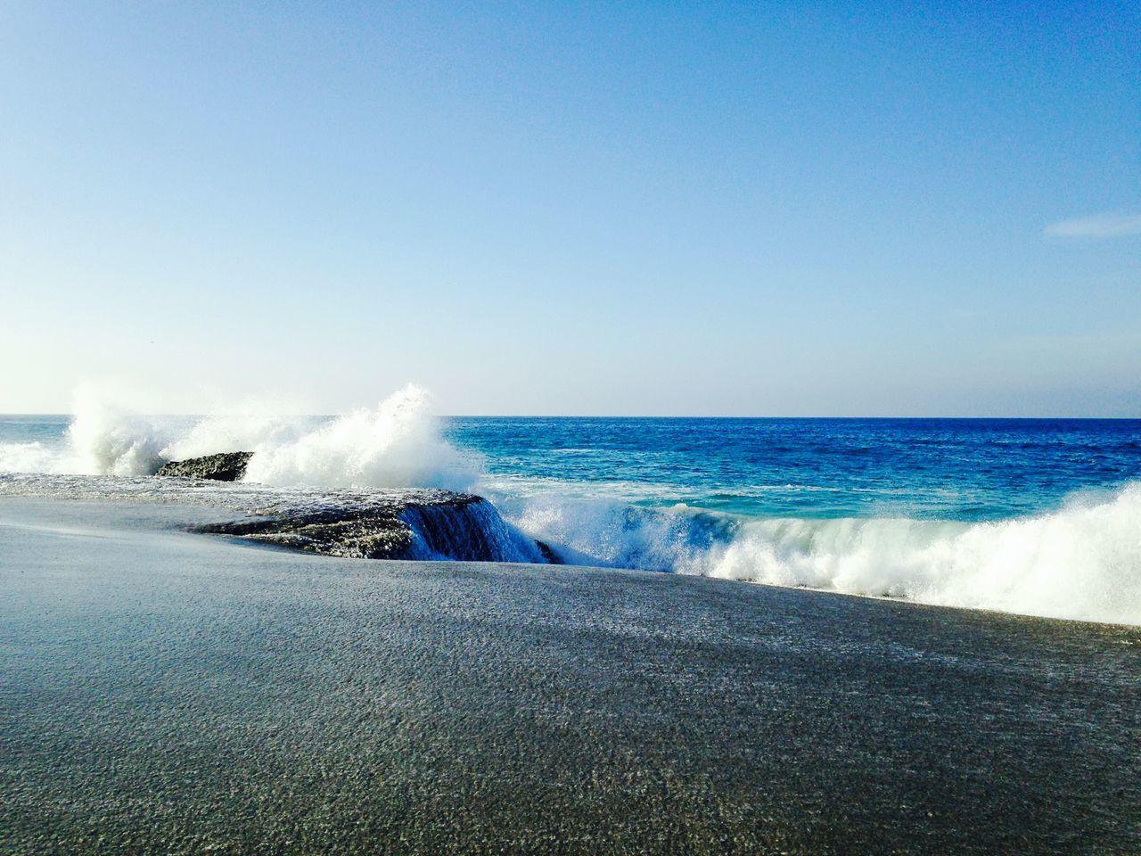 Sea Waves Splashing On Shore Against Clear Sky