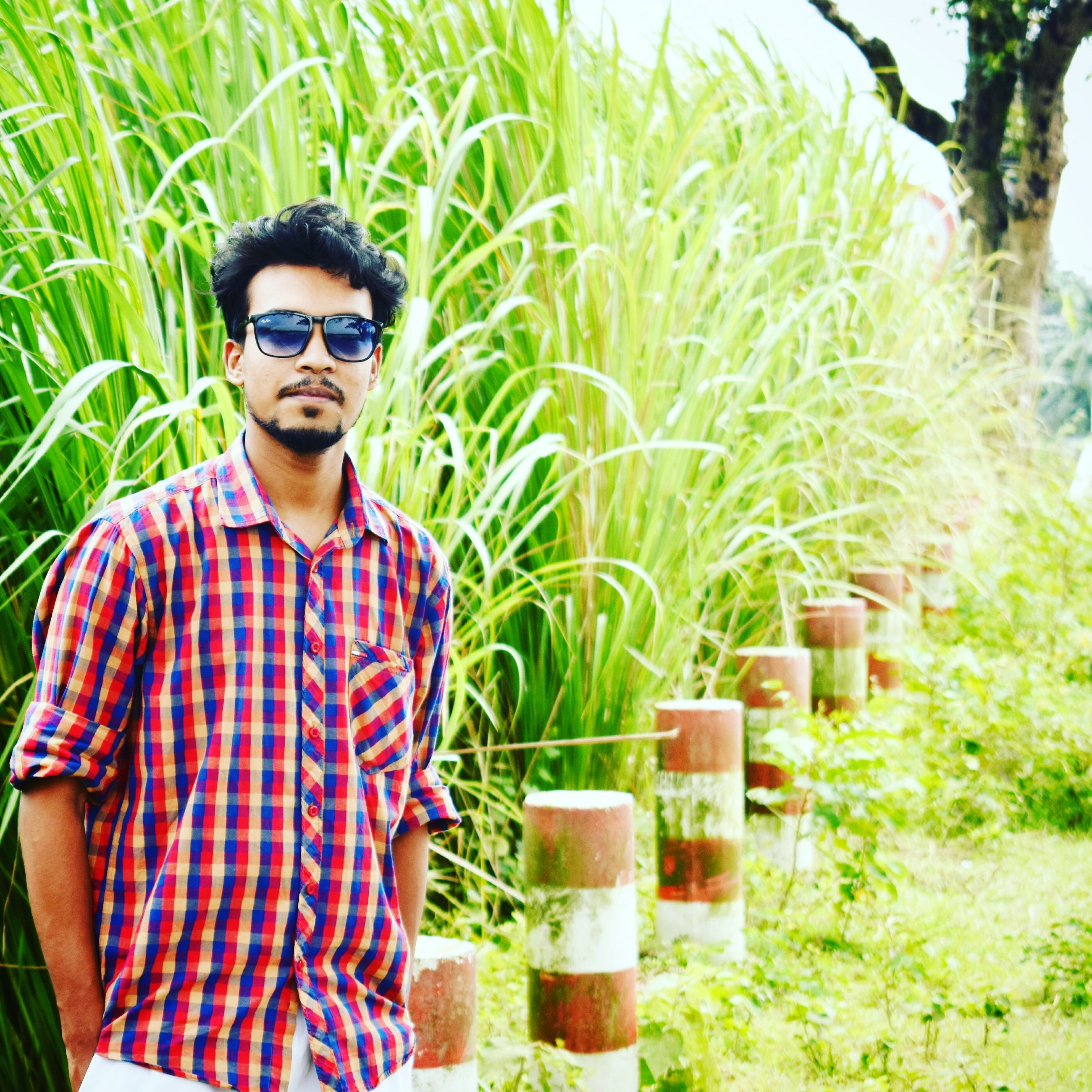 sunglasses, one person, checked pattern, grass, one man only, one young man only, only men, young adult, adults only, day, portrait, outdoors, leisure activity, standing, looking at camera, young men, vacations, adult, real people, eyeglasses, people, nature