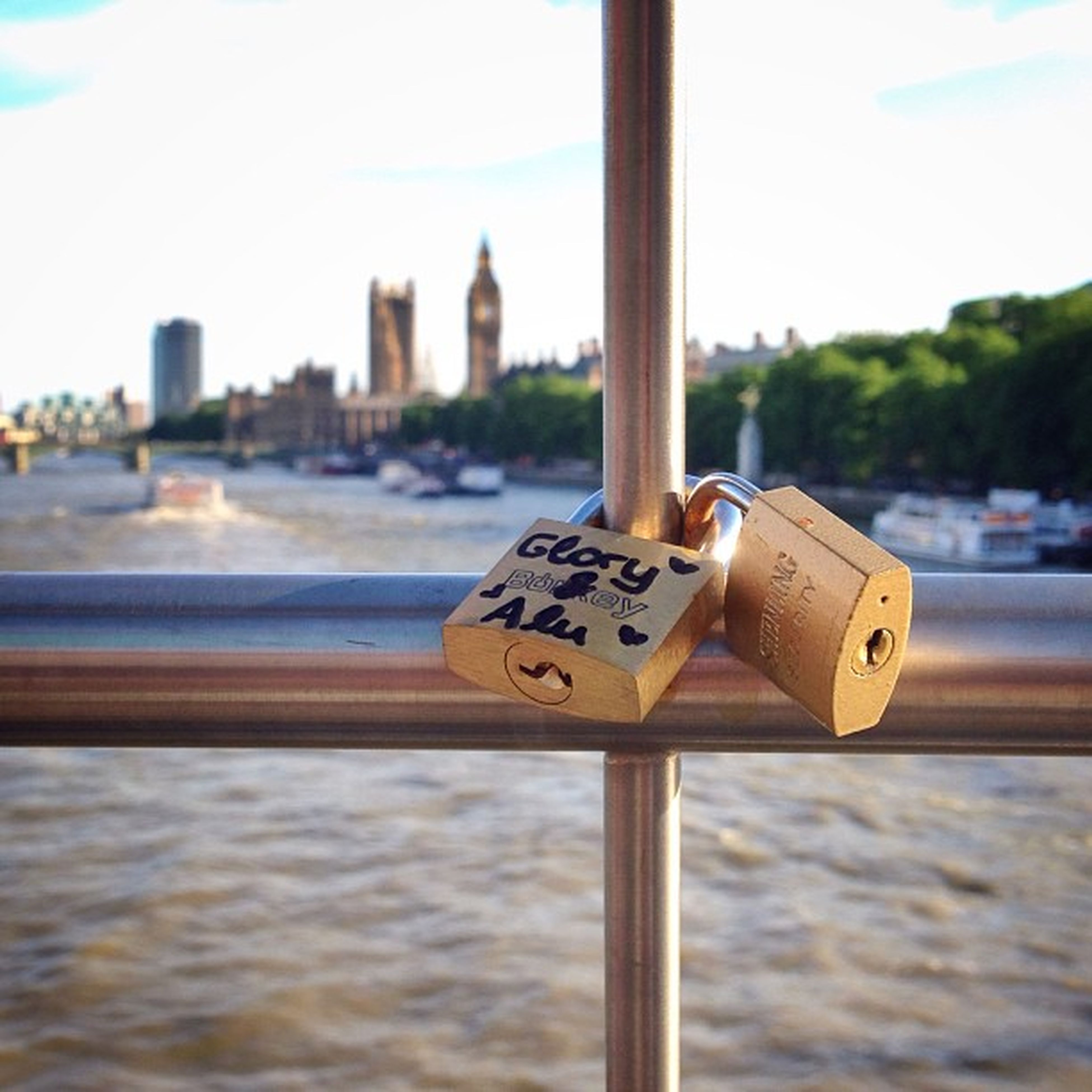 focus on foreground, text, communication, metal, close-up, western script, padlock, day, selective focus, sky, pole, water, no people, safety, river, built structure, outdoors, metallic, guidance, architecture