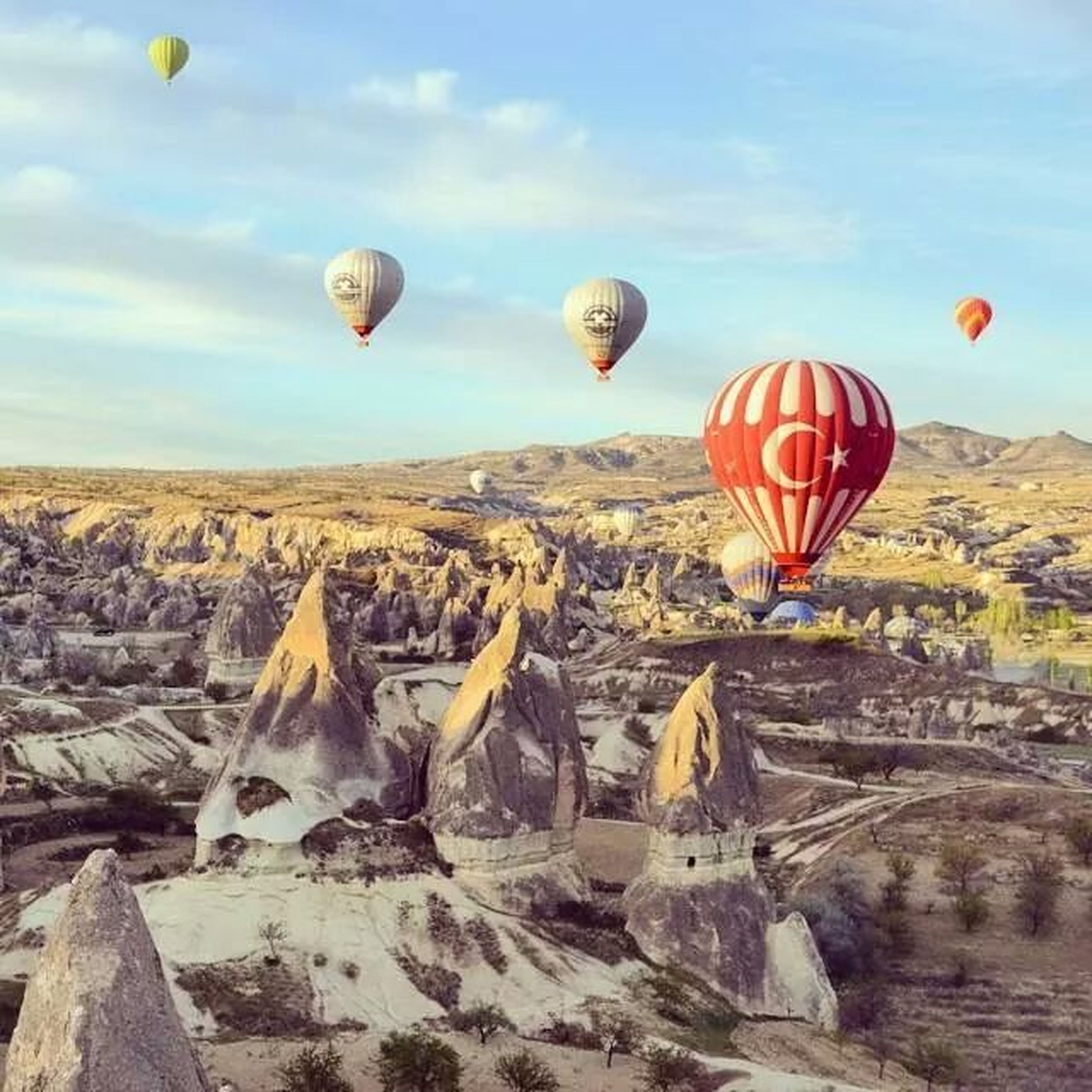 hot air balloon, mid-air, flying, sky, parachute, adventure, landscape, scenics, paragliding, tranquil scene, tranquility, extreme sports, leisure activity, sport, nature, transportation, multi colored, beauty in nature, rock - object