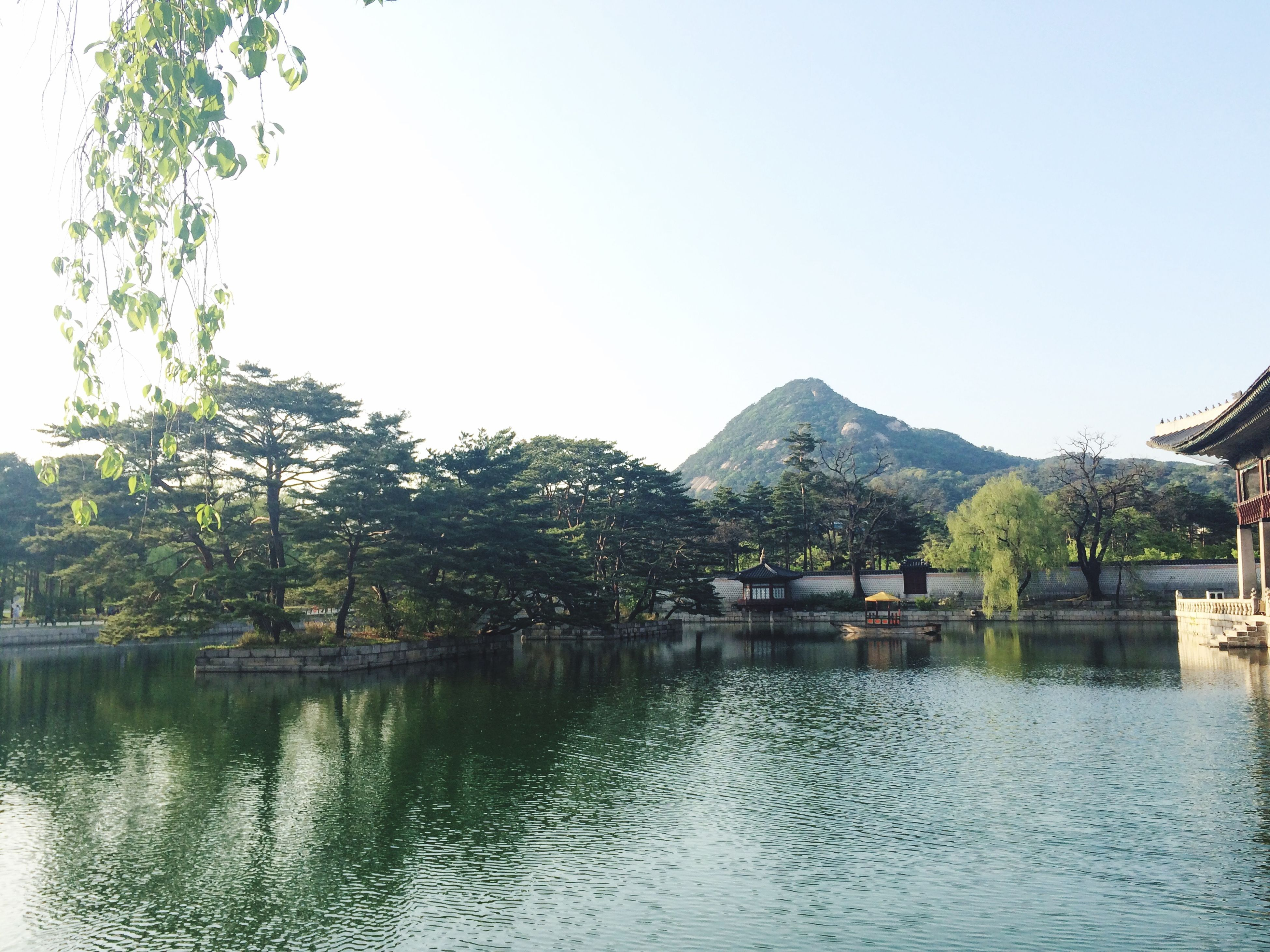 clear sky, water, mountain, waterfront, tree, lake, tranquil scene, copy space, tranquility, scenics, built structure, nature, beauty in nature, river, mountain range, reflection, architecture, building exterior, day, idyllic