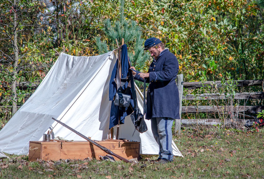 oct 8, 4th Annual Mooresville Civil War Days , South Haven, Michigan; a union soldier at his camp site prepares for battle during a civil war reenactment Camping Civil War Michigan, USA USA Uniform Adult Blue Day Editorial  Guns History Men Military Nature One Person Outdoors People Reenactment Standing Tent Union Soldier War Weopons Working