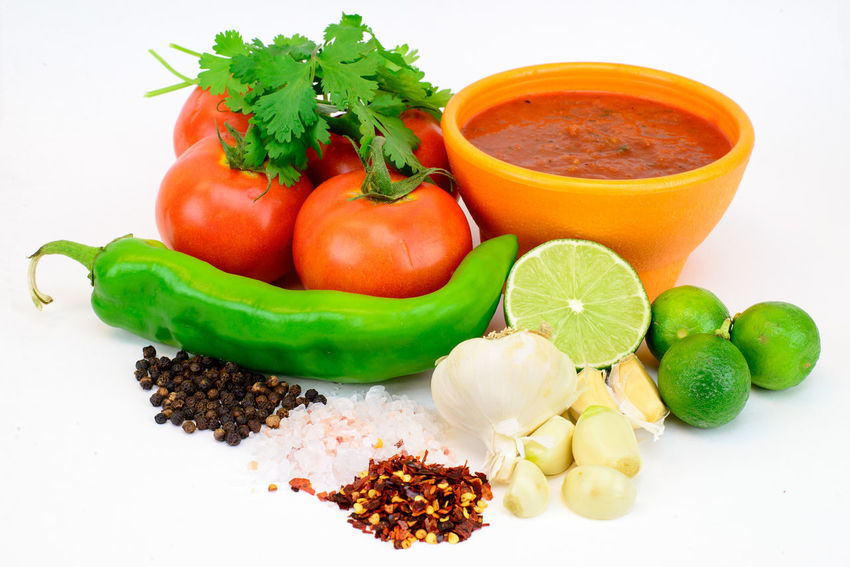 A fresh bowl of Salsa and the ingredients that made it Garlic Limes Red Pepper Salt Black Peppercorns Cilantro Close-up Food Food And Drink Freshness Garlic Cloves Green Color Healthy Eating Ingredient Lime Molcajete No People Peppers Red Pepper Flakes Salsa Spice Tomato Tomatoes Vegetable White Background