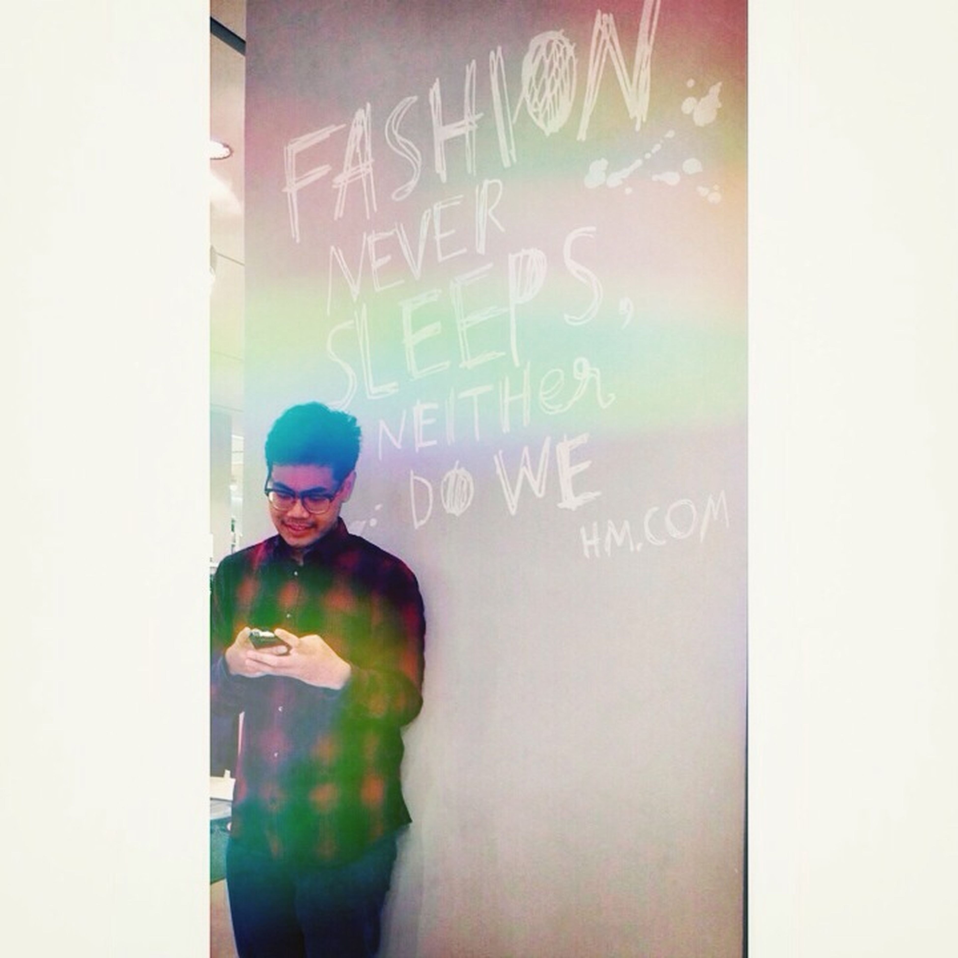 text, western script, communication, wall - building feature, lifestyles, graffiti, young adult, leisure activity, waist up, creativity, non-western script, front view, art, wall, standing, indoors, human representation, person