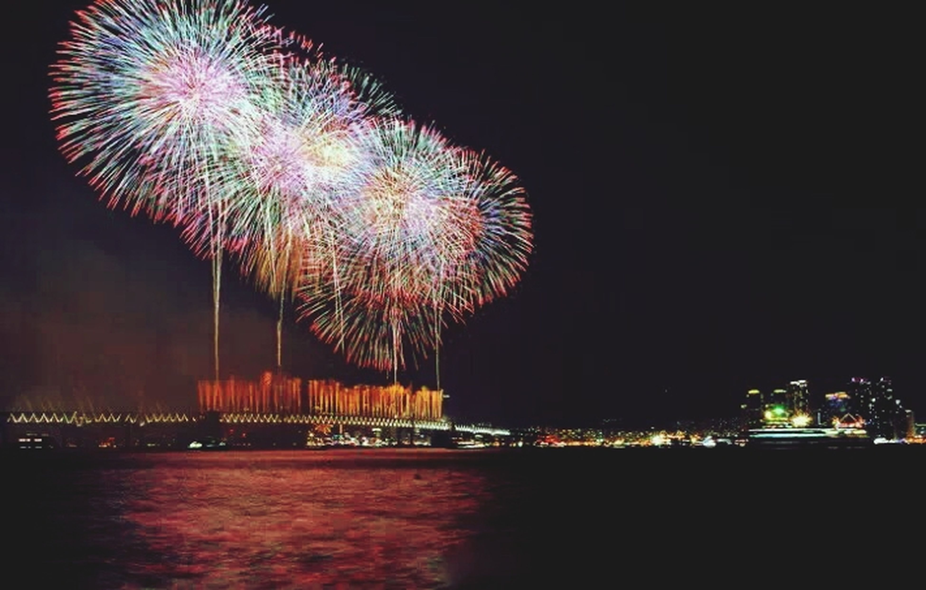 illuminated, night, long exposure, firework display, exploding, celebration, motion, arts culture and entertainment, firework - man made object, glowing, sparks, water, event, blurred motion, sky, multi colored, building exterior, river, city, waterfront