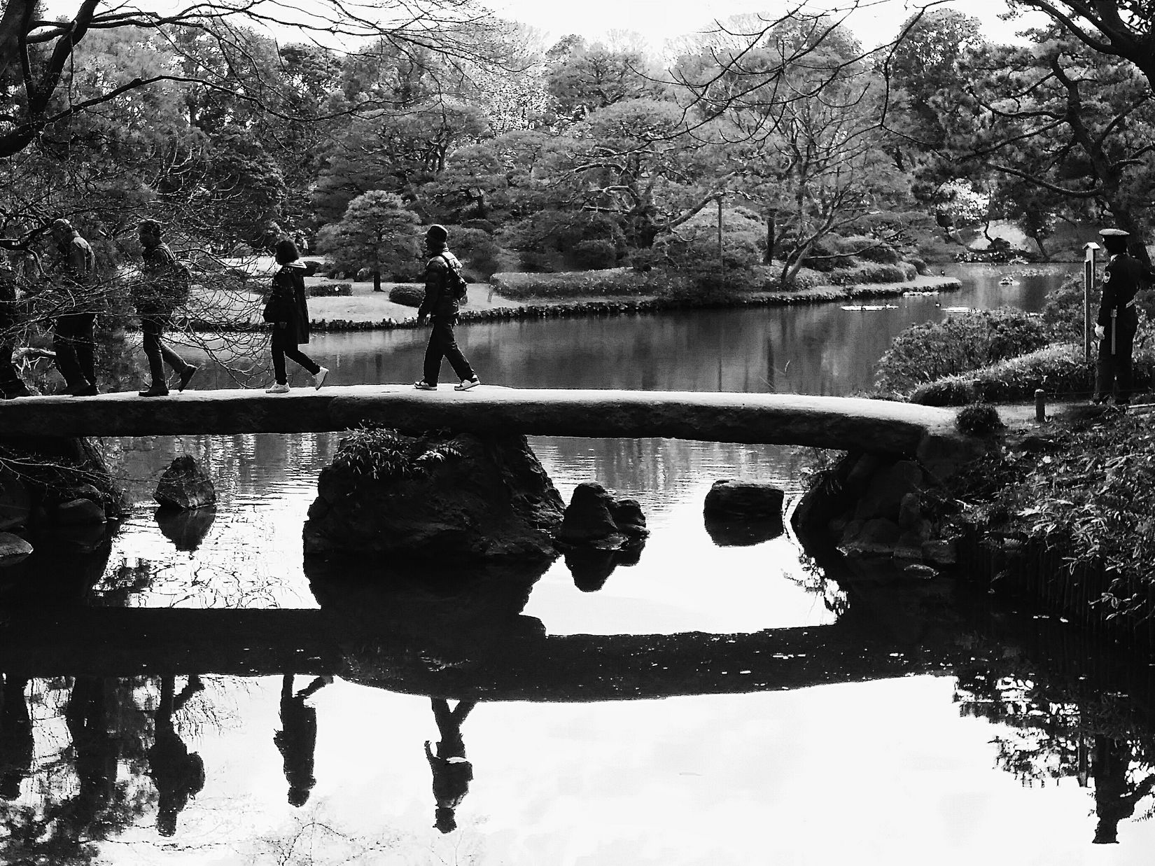 The guard stands on the right of the bridge, directing (single-file) traffic flow on the bridge Reflections Crossing The Bridge Bridge Guard Rikugien Garden Rikugienspring2016 Edo Garden Tokyo Tokyospring2016 Japan Japanese Culture Orderly Carefulness Consideration Streetphotography Bnw Bnw_capture Bnw_life Bnw_collection Bnw_globe Bnw_streetphotography Eyeem Photography EyeEM Tokyo Eyeem Nature Eyeem Spring