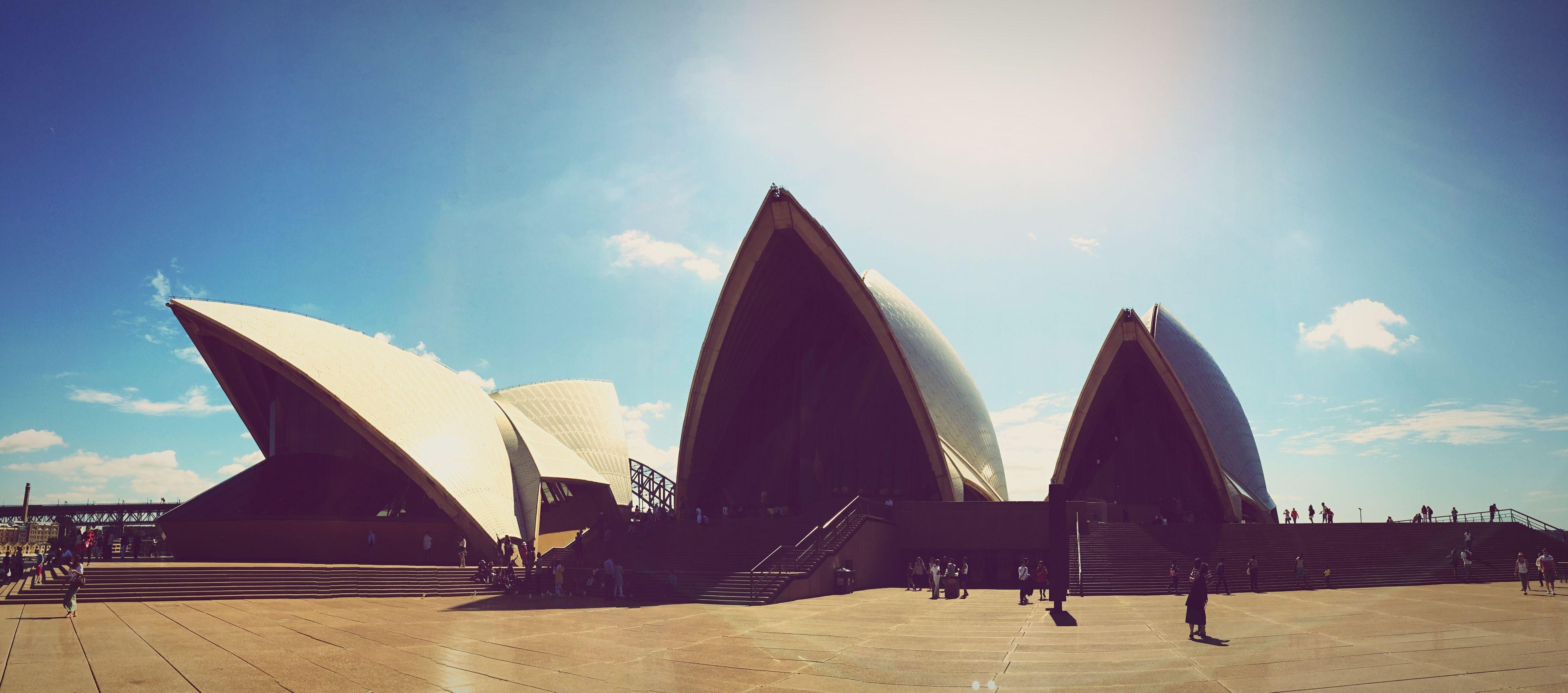 sky, built structure, architecture, sunlight, building exterior, cloud - sky, famous place, low angle view, blue, travel destinations, tourism, cloud, travel, leisure activity, incidental people, sunny, day, men, shadow