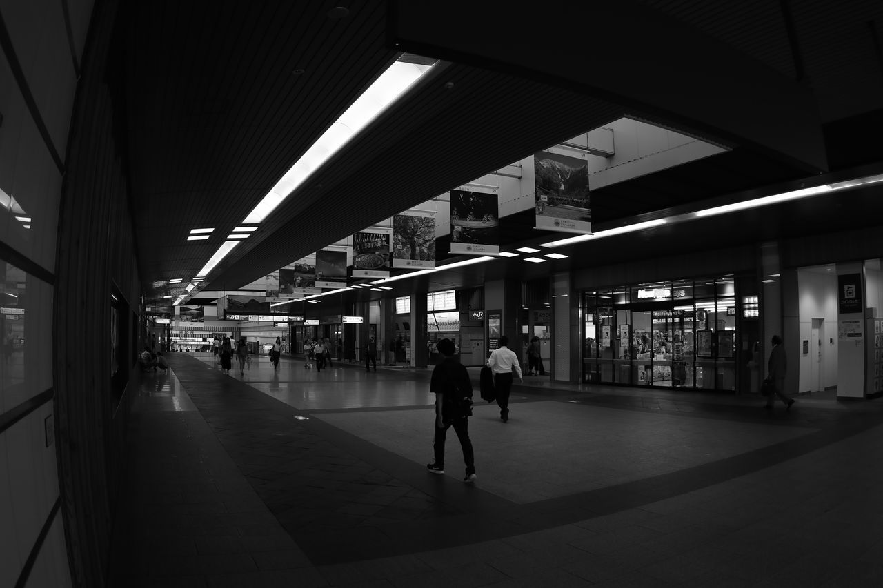 real people, illuminated, railroad station, built structure, transportation, architecture, women, railroad station platform, public transportation, indoors, walking, lifestyles, men, group of people, architectural column, night, full length, city, adult, people
