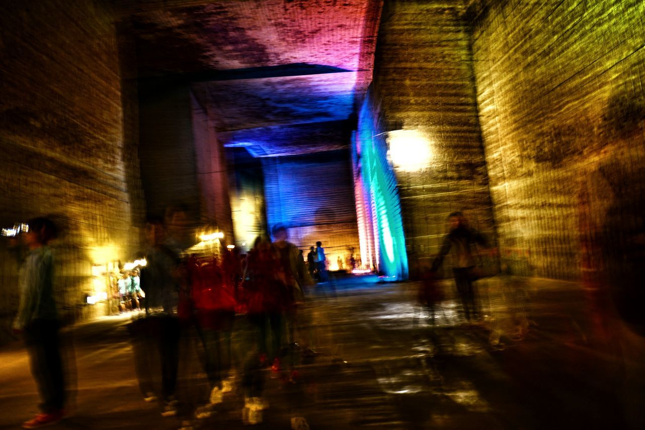 real people, large group of people, walking, illuminated, blurred motion, men, women, built structure, lifestyles, architecture, leisure activity, indoors, group of people, night, people, adult