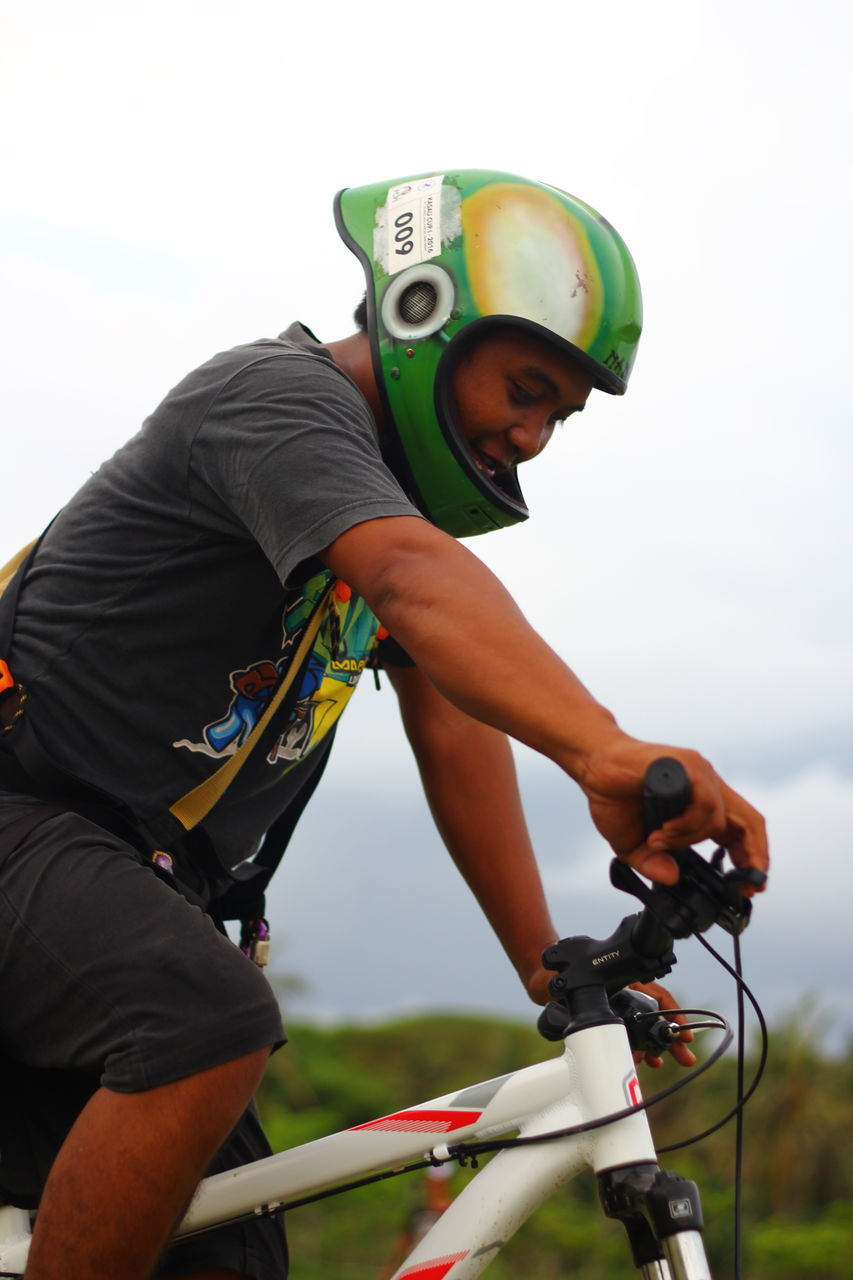 real people, riding, leisure activity, safety, adventure, helmet, one person, boys, sport, balance, childhood, sports helmet, lifestyles, extreme sports, day, outdoors, headwear, cycling, cycling helmet, bicycle, skill, low angle view, competition, sky, people