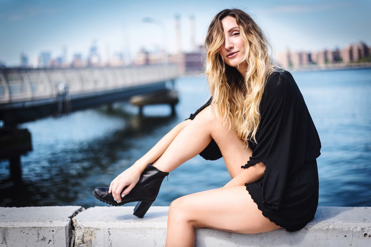 Sitting One Person Leisure Activity Beautiful Woman Water Casual Clothing Bridge - Man Made Structure Outdoors Focus On Foreground Day Full Length Built Structure Young Adult Real People Architecture Lifestyles Smiling Happiness Retaining Wall Nautical Vessel Photooftheday Fashion Photographer Model NYC
