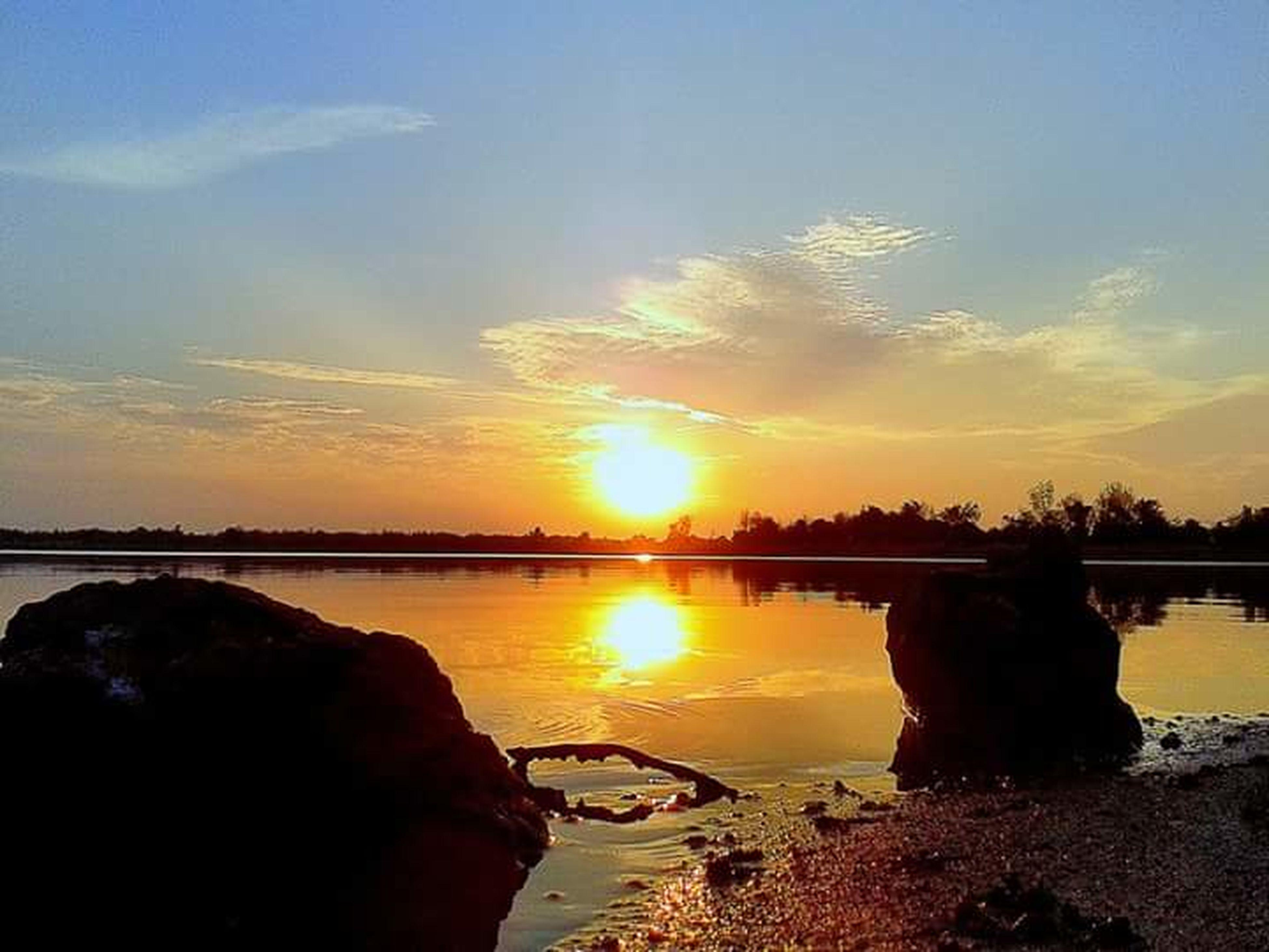 sunset, water, sun, sky, reflection, scenics, tranquil scene, tranquility, beauty in nature, rock - object, silhouette, nature, orange color, sea, sunlight, idyllic, beach, cloud - sky, shore, lake