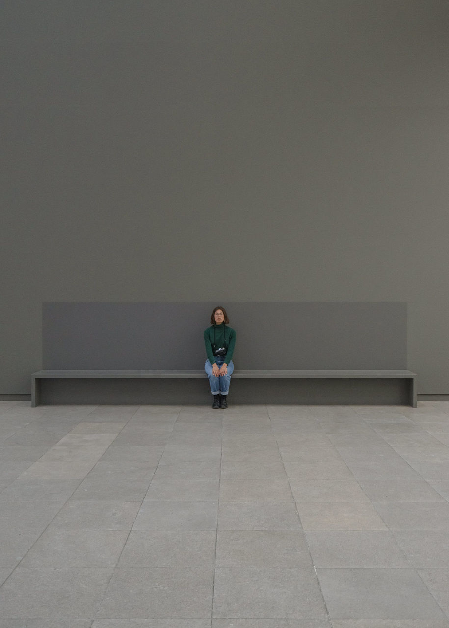 full length, real people, one person, front view, lifestyles, young women, young adult, sitting, waiting, indoors, day